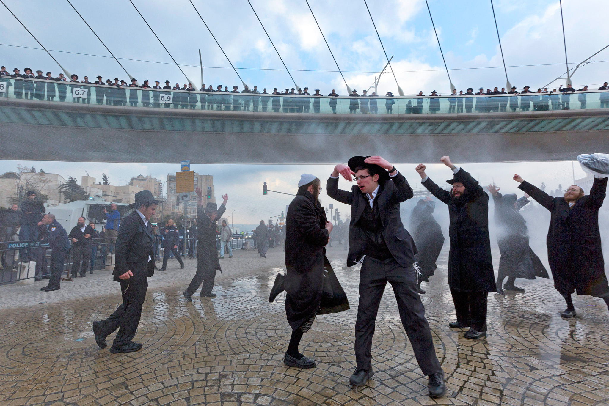 epa04057945 Ultra-Orthodox Jews dance as police fire a water canon at them during a protest at the entrance to Jerusalem, 06 February 2014, over Israel drafting ultra-Orthodox into the the military. Several thousand ultra-Orthodox protested in Jerusalem and other Israeli cities and towns after an ultra-Orthodox Jewish young man was arrested when he dodged the draft. Police used water canon and horses and physical force to break up the protest.