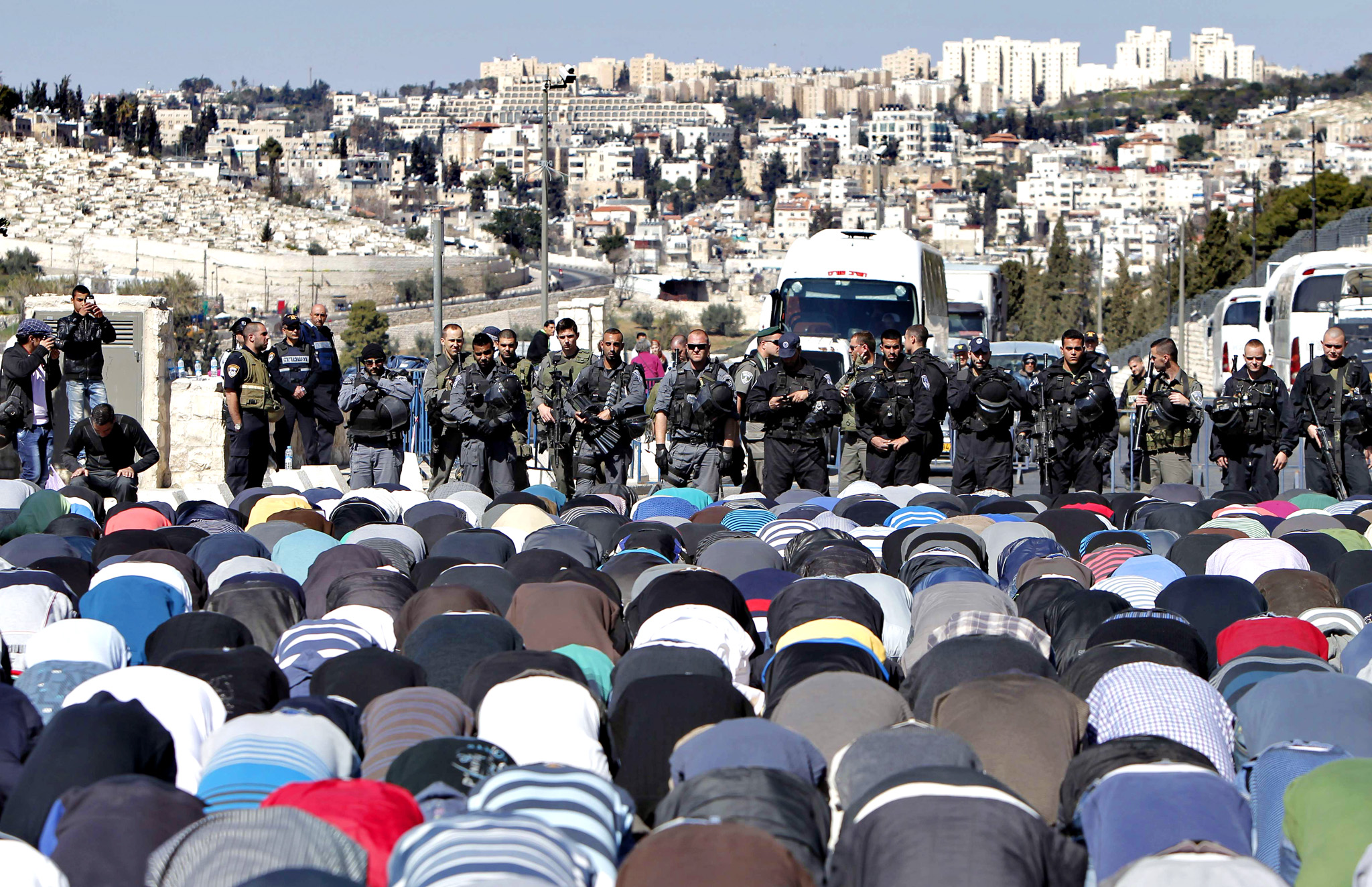 Muslim Palestinians take part in Friday noon prayers blocked by Israeli police in East Jerusalem neighborhood of Ras al-Amud, on February 28, 2014. Clashes broke out following Friday noon prayer three days after police clashed with stone-throwing Palestinians at the al-Aqsa mosque compound, hours ahead of a debate in the Israeli parliament on Jews' right to pray at the compound, which is currently denied. The flashpoint compound sits above the Western Wall plaza and houses the Dome of the Rock and the Al-Aqsa mosque, and is Islam's third-holiest site.  AFP PHOTO / AHMAD GHARABLIAHMAD GHARABLI/AFP/Getty Images