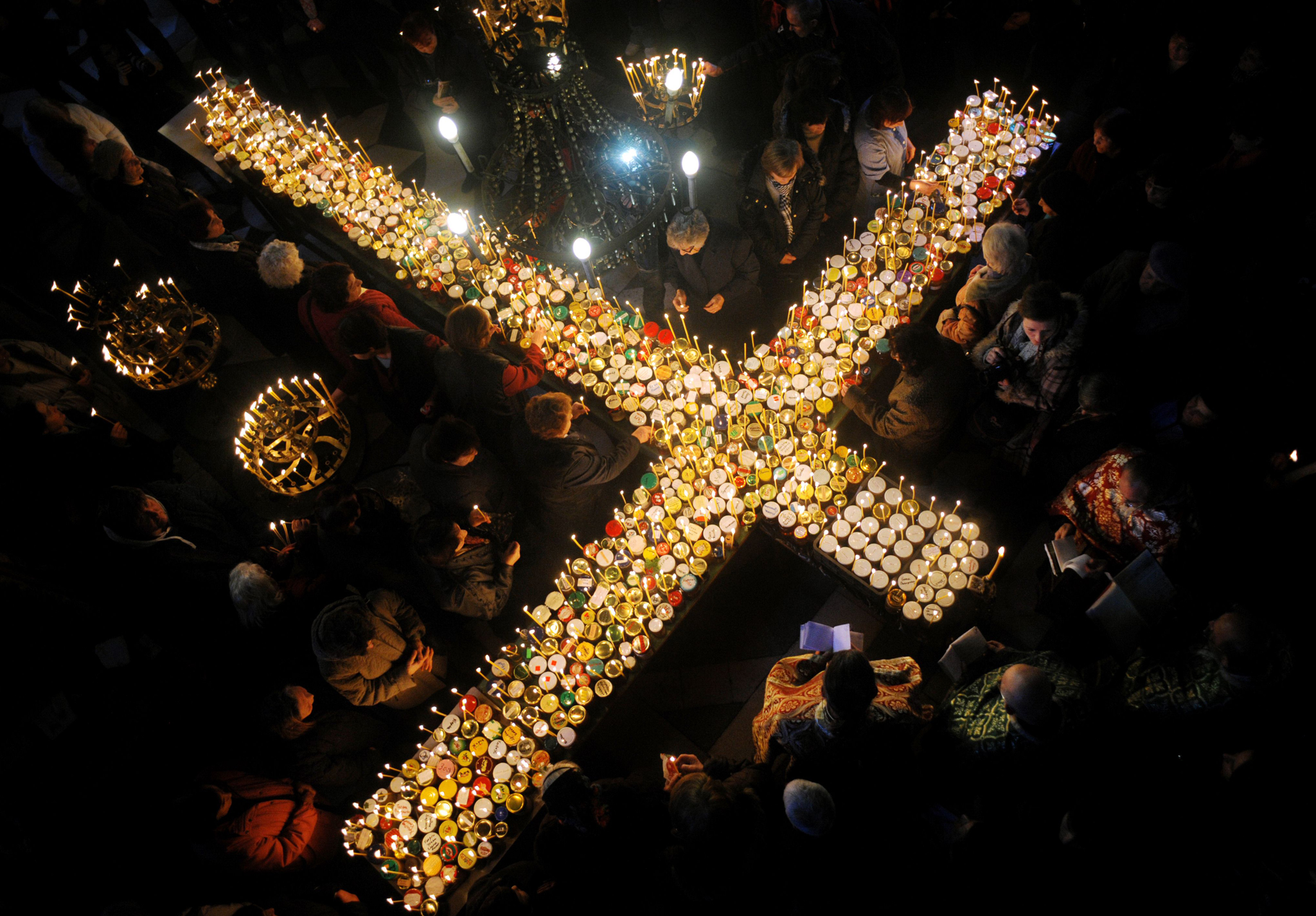 Believers pray around a cross-shaped platform covered with candles placed in jars of honey during a celebration in of St. Haralampi, protector of beekeepers, at the Church of the Blessed Virgin in Blagoevgrad, eastern Bulgaria