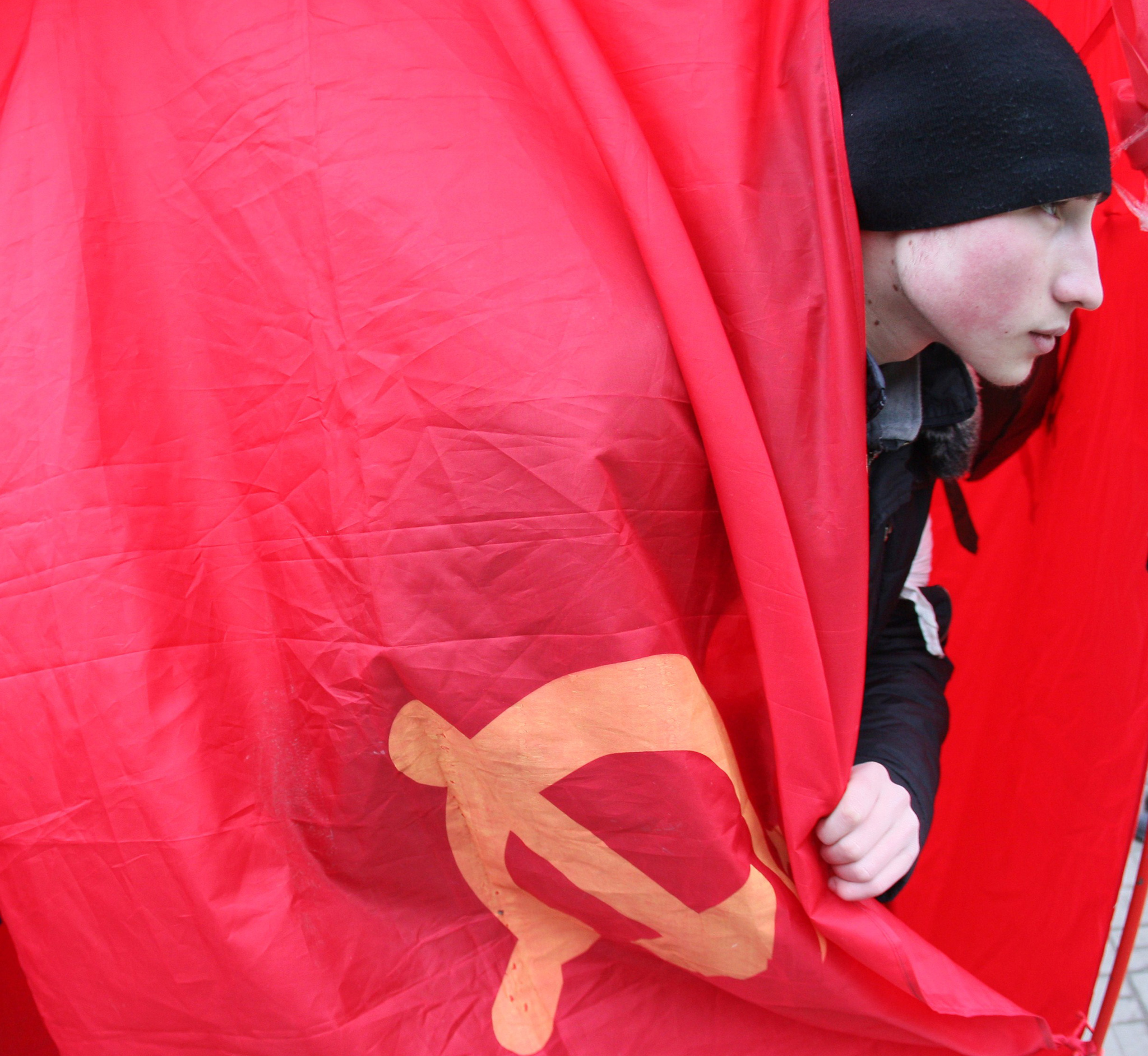 "A young activist wraps himself in a Soviet-era communist flag as pro-Russian activists from the so called ""Eastern Front"" movement take part in a rally in front of the Lenin monument in the center of the industrial Ukrainian city of Donetsk"