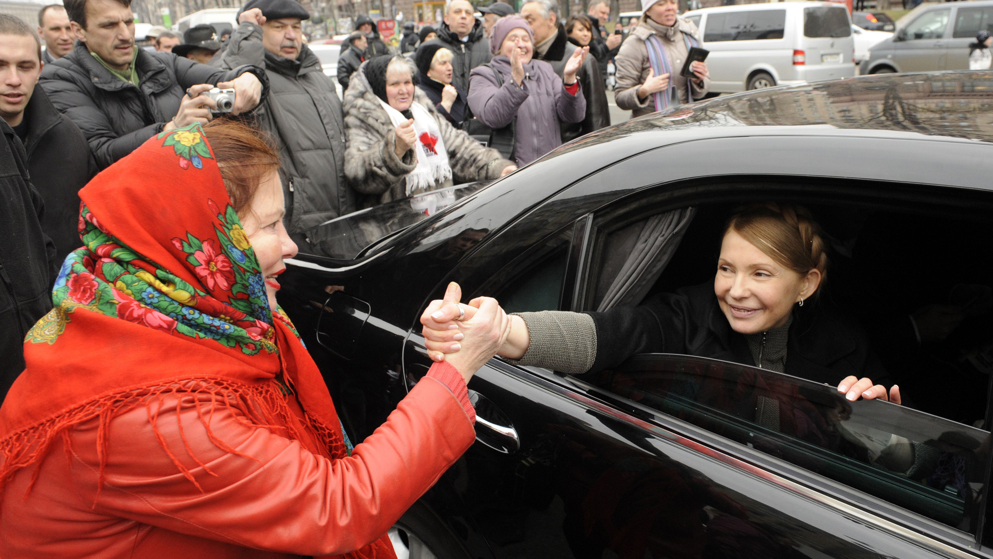 Ukrainian opposition leader Yulia Tymoshenko shakes hands with a woman as she arrives to visit the tent camp of her supporters in the center of Kiev .