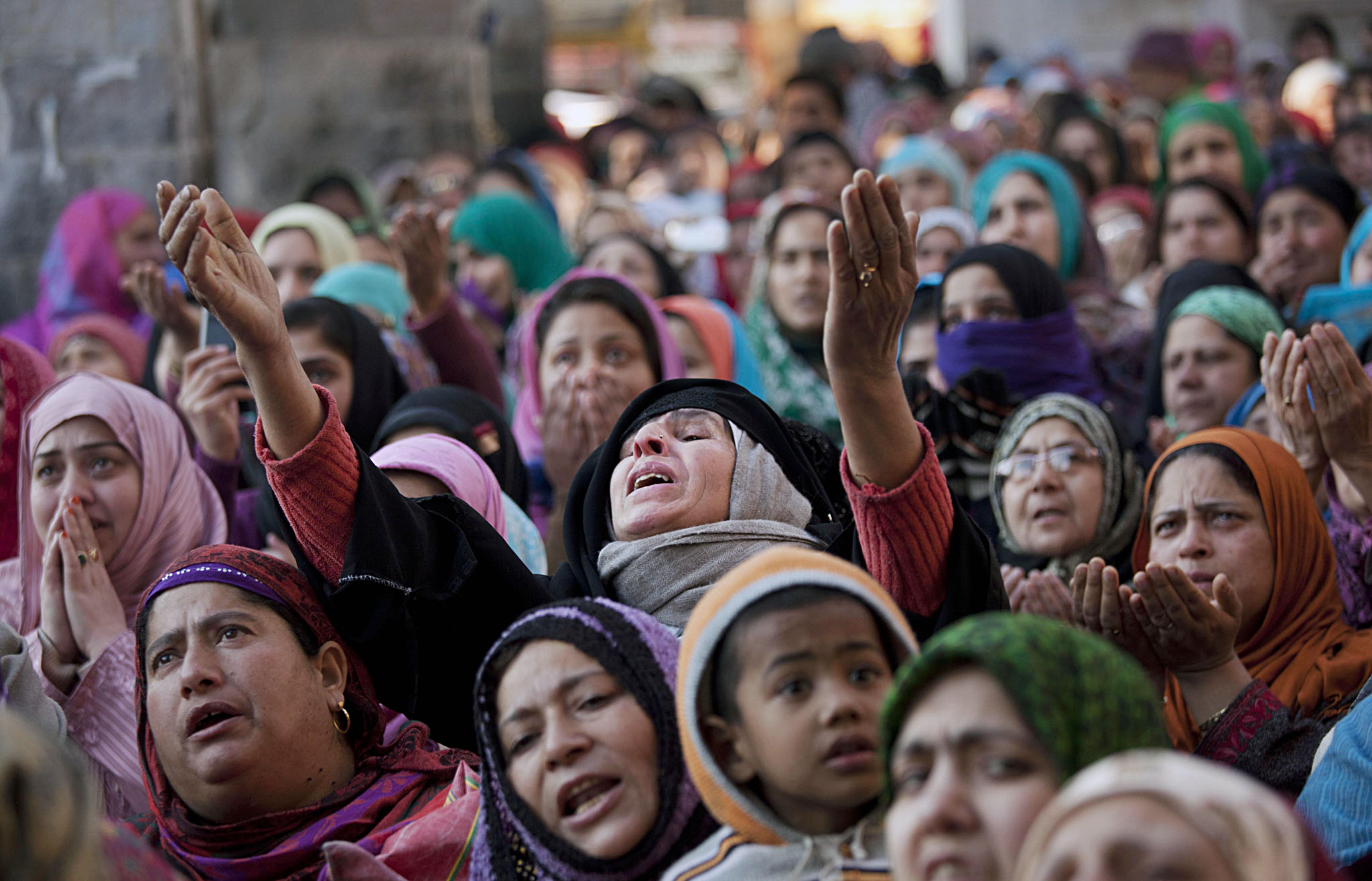Kashmiri Muslim devotees pray as the head priest displays a relic of Syed Abdul Qadir Jilani outside his shrine in Srinagar, India, Thursday, Feb. 13, 2014. Hundreds of devotees thronged the shrine which houses the relic of the saint to mark the saint's Urs, or yearly commemoration. (AP Photo/ Dar Yasin)