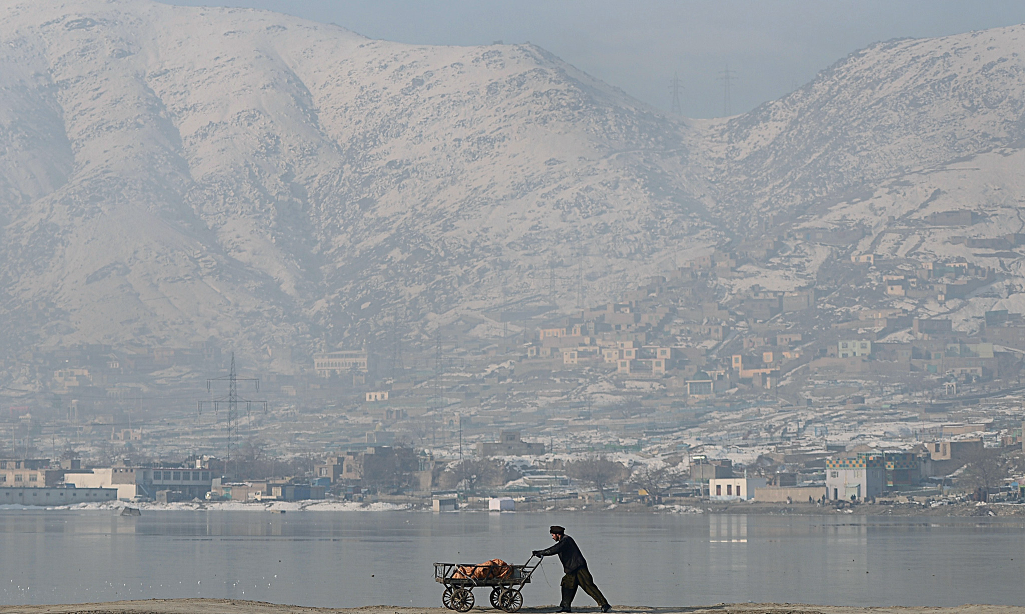 An Afghan man pushes his cart at Shuhada...An Afghan man pushes his cart at Shuhada Lake in Kabul on February 10, 2014.   Afghanistan's economy is recovering from decades of conflict but despite the significant improvement in the last decade it is extremely poor, landlocked, and highly dependent on foreign aid.   AFP PHOTO/ Wakil KohsarWAKIL KOHSAR/AFP/Getty Images