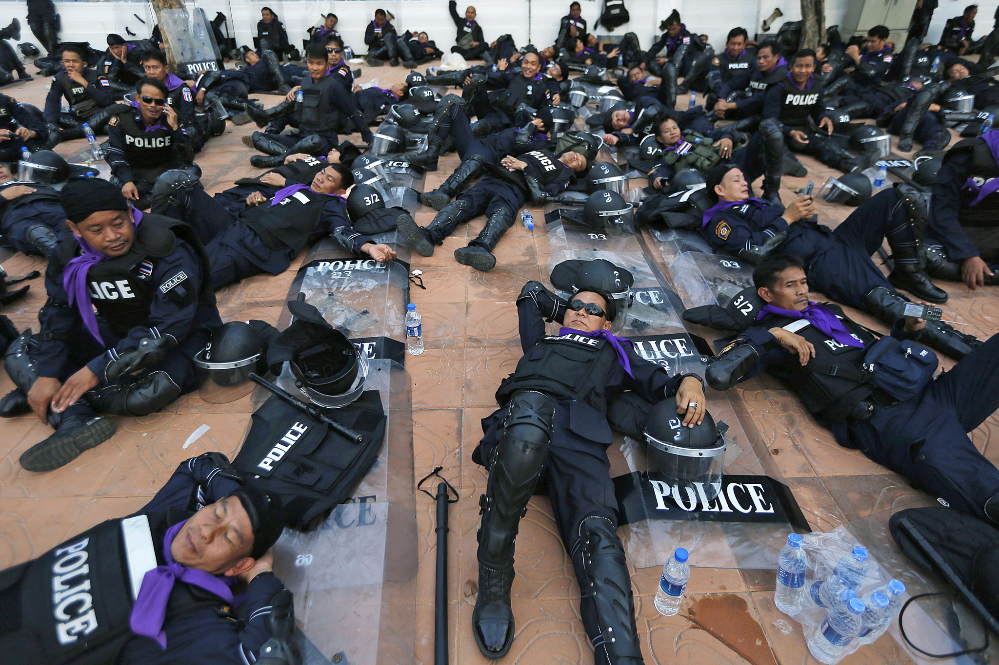 Riot police take a rest with their equipment before moving into anti-government encampment near the Government House in central Bangkok...Riot police take a rest with their equipment before moving into anti-government encampment near the Government House in central Bangkok February 14, 2014. Thousands of Thai riot police were deployed on Friday to seize back protest sites around government buildings in Bangkok that have been occupied for months by demonstrators seeking to topple Prime Minister Yingluck Shinawatra.  REUTERS/Damir Sagolj