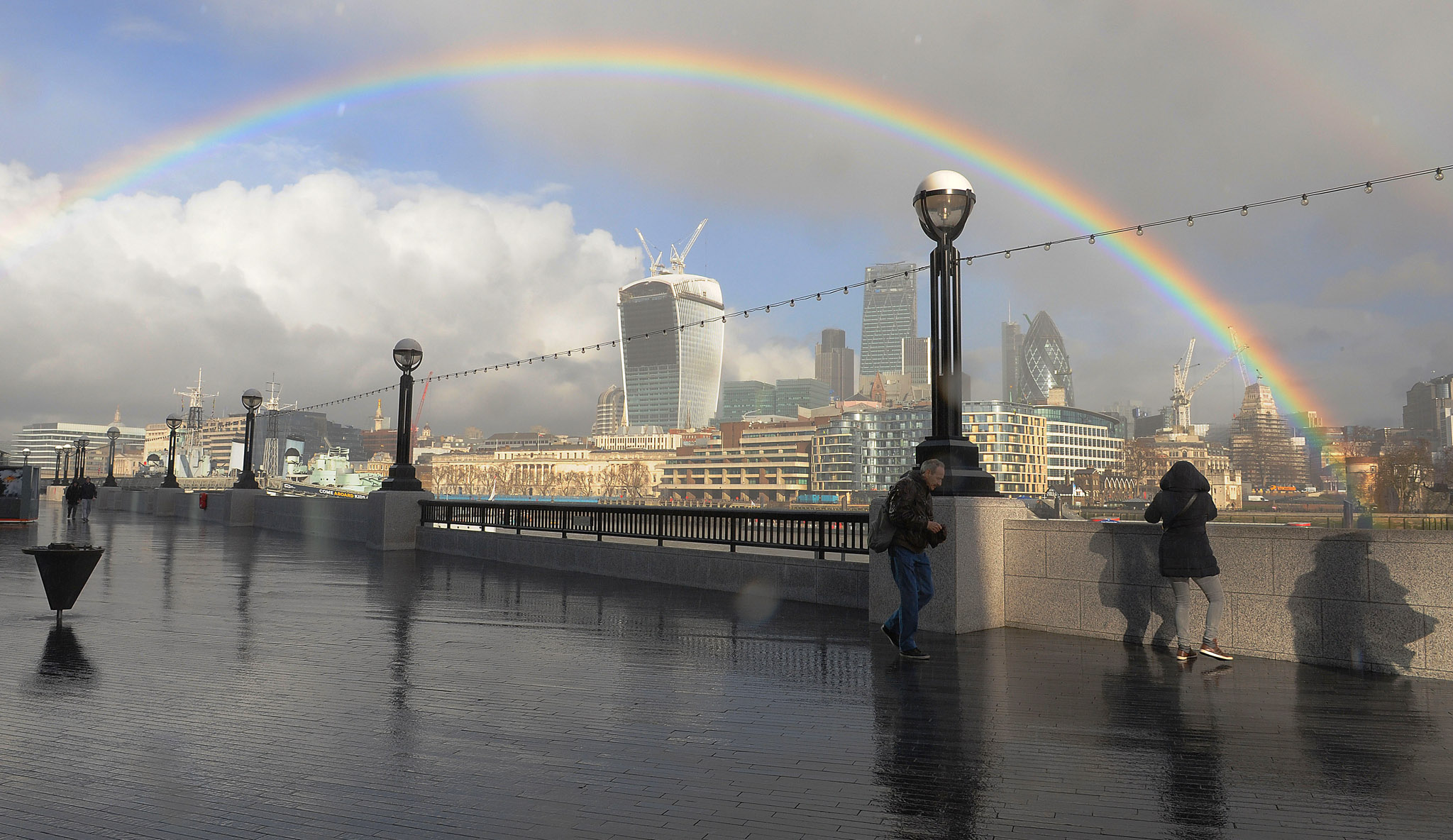 Winter weather Feb 4th...People walk along the Southbank as a rainbow appears over the city of London. PRESS ASSOCIATION Photo. Picture date: Tuesday February 4, 2014.