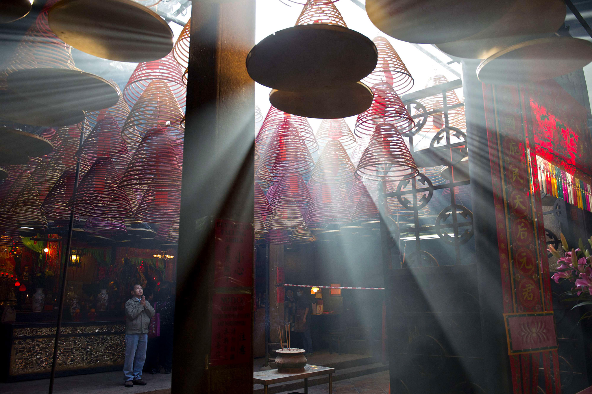 A man (R) prays as sunlight shines throu...A man (R) prays as sunlight shines through hanging incense coils at the Tin Hau Temple in the Yau Ma Tei area of Hong Kong on the fourth day of the Lunar New Year holiday on February 3, 2014.  Chinese communities across Asia came together to usher in the Year of the Horse, with tens of thousands of worshippers flocking to temples across China to pray for good fortune in the new year.