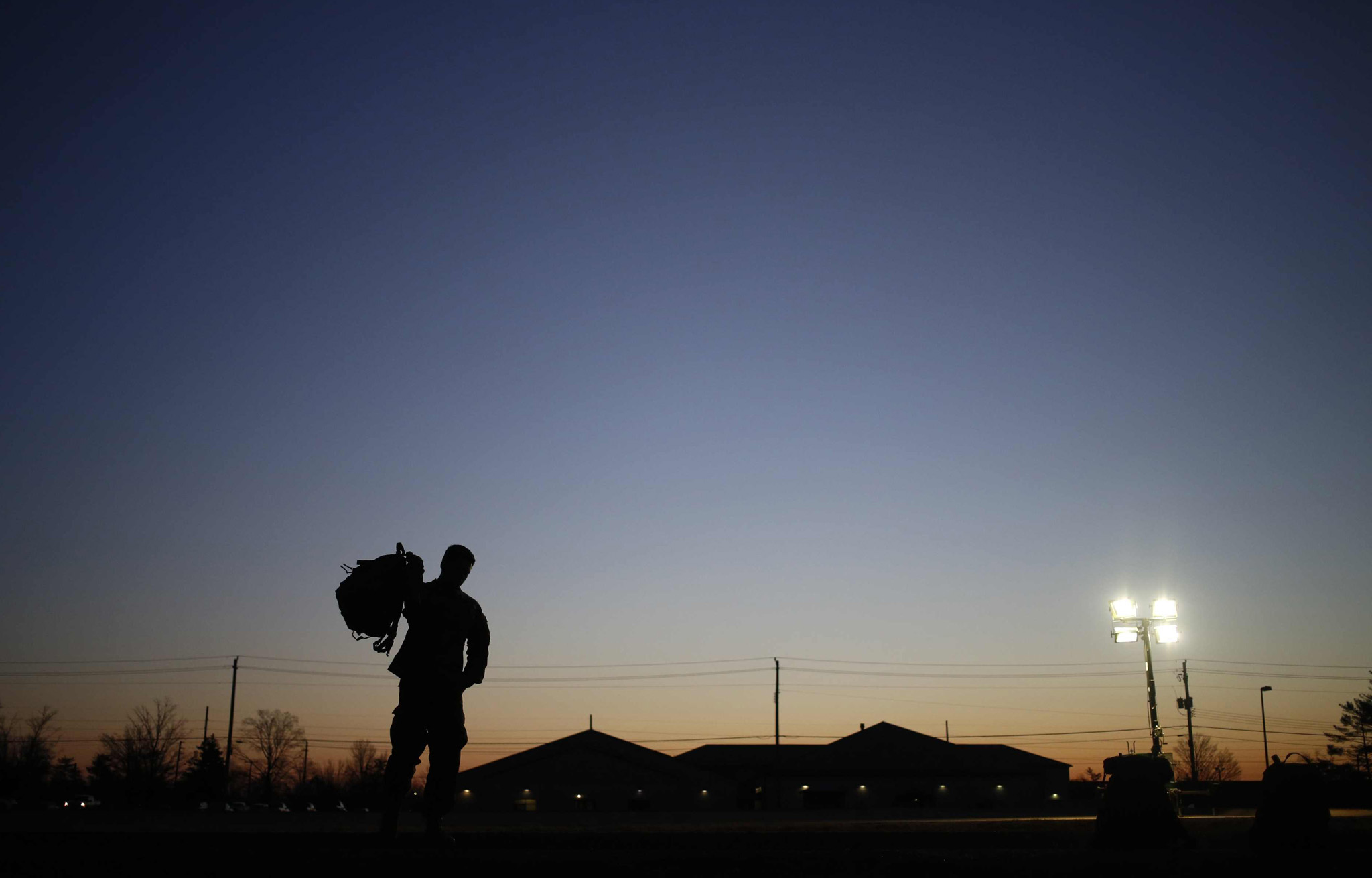 A soldier from the U.S. Army's 3rd Brigade Combat Team, 1st Infantry Division, grabs his rucksack following a homecoming ceremony in the Natcher Physical Fitness Center, Fort Knox, Kentucky. About 100 soldiers returned to Fort Knox after a nine-month combat deployment conducting village stability operations and working alongside Afghan military and police forces.