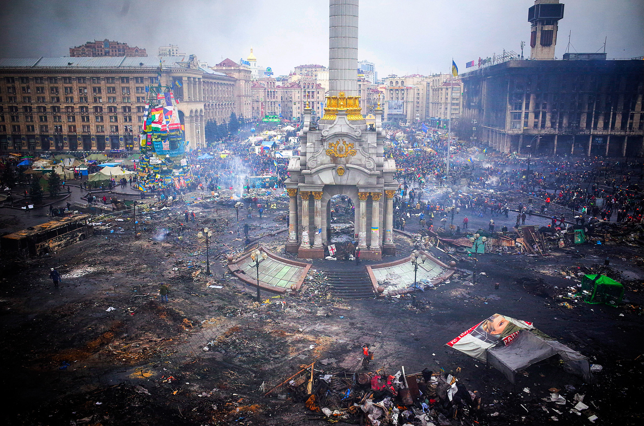 General Economy As Escalating Unrest Tumbles Currency And Shares...Protestors inspect damage caused by recent anti-government protests on Independence Square following recent clashes in Kiev, Ukraine, on Thursday, Feb. 20, 2014. Violence is escalating in the country of 45 million as the Russian-backed leader's security service conducts a nationwide anti-terrorism operation to end the three-month uprising. Photographer: Vincent Mundy/Bloomberg