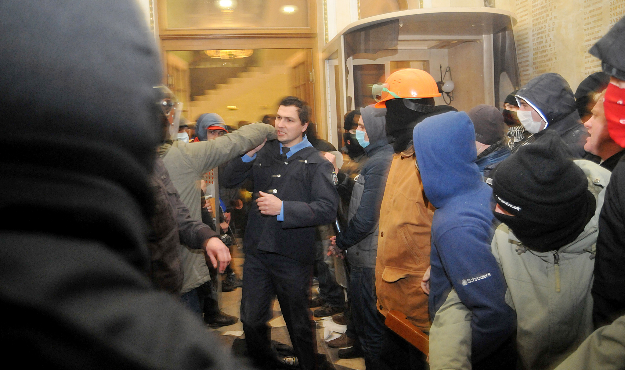 A policeman, center, tries to stop Ukrainian protesters as they seize police headquarters in Lviv, western Ukraine, early Wednesday, Feb. 19, 2014. The violence on Tuesday was the worst in nearly three months of anti-government protests that have paralyzed Ukraine's capital, Kiev, in a struggle over the identity of a nation divided in loyalties between Russia and the West, and the worst in the country's post-Soviet history. (AP Photo/ Pavlo Palamarchuk)