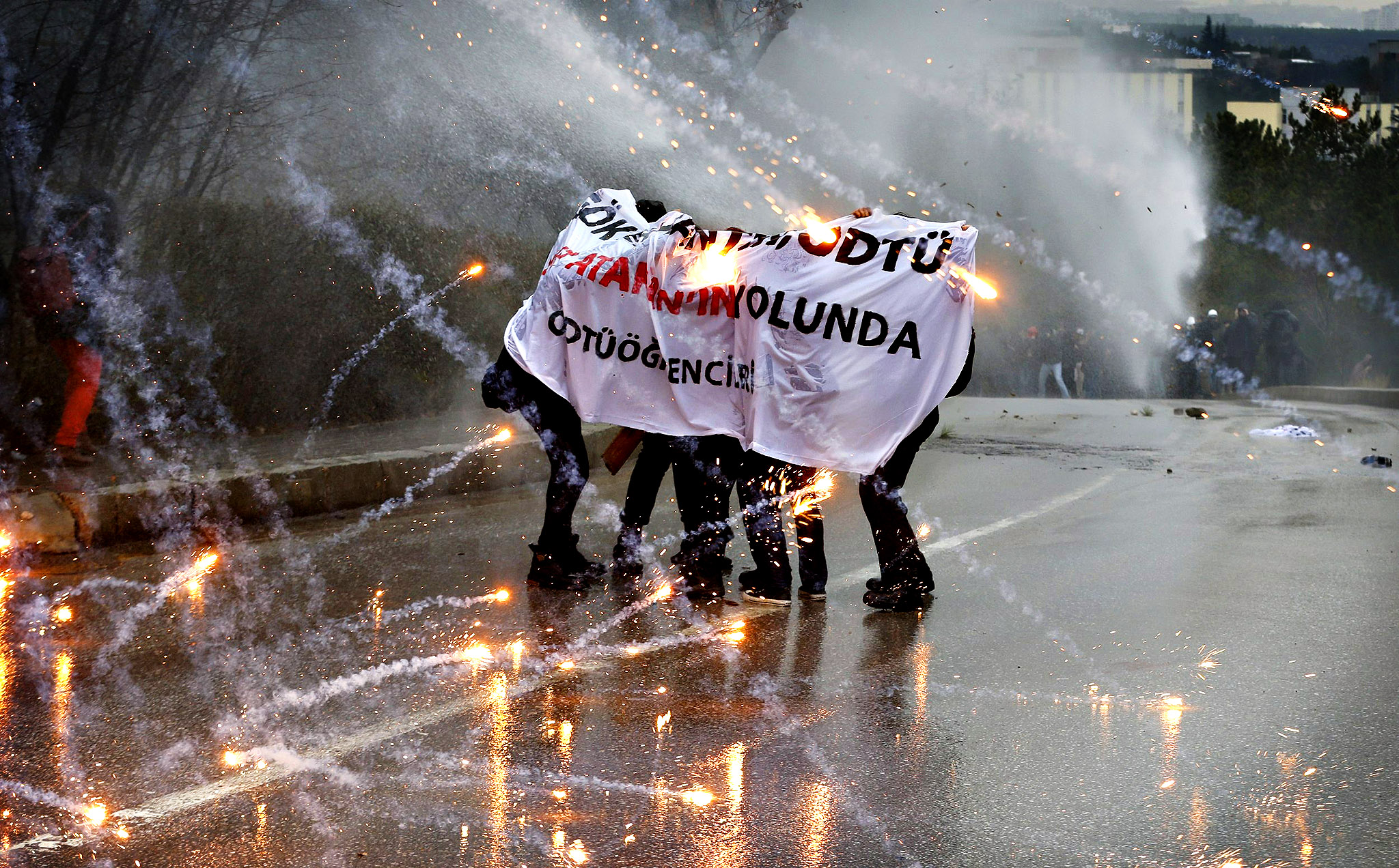 Demonstrators take cover from a police water cannon as fireworks, thrown by other protesters, explode around them during a demonstration against the opening of a new road including a part of the Middle East Technical University campus in Ankara...Demonstrators take cover from a police water cannon as fireworks, thrown by other protesters, explode around them during a demonstration against the opening of a new road including a part of the Middle East Technical University campus in Ankara February 25, 2014. Erdogan opened the road across the Middle East Technical University campus and uprooting a large number of trees in the area in Ankara on Tuesday.