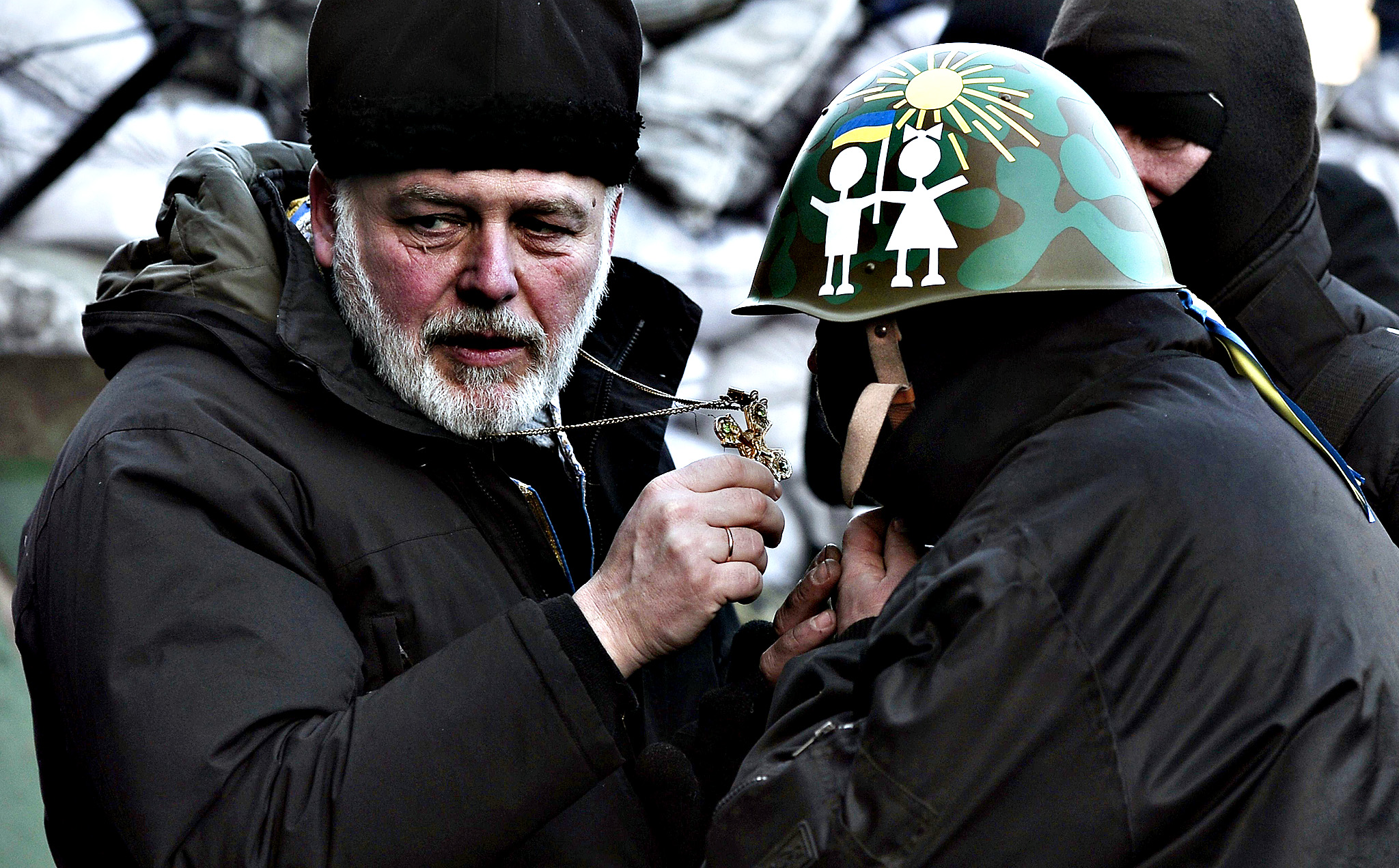A priest blesses an anti-government protester at a road block in Kiev on February 5, 2014. Ukraine's parliament will try again on February 5 to agree on curbing the presidency's powers, while the EU's foreign policy chief met embattled President Viktor Yanukovych to press for a resolution of the political crisis. The crisis has sparked tensions between the West, which is considering sanctions against Ukrainian officials, and Russia, which has accused the EU and US of interference in the former Soviet republic.