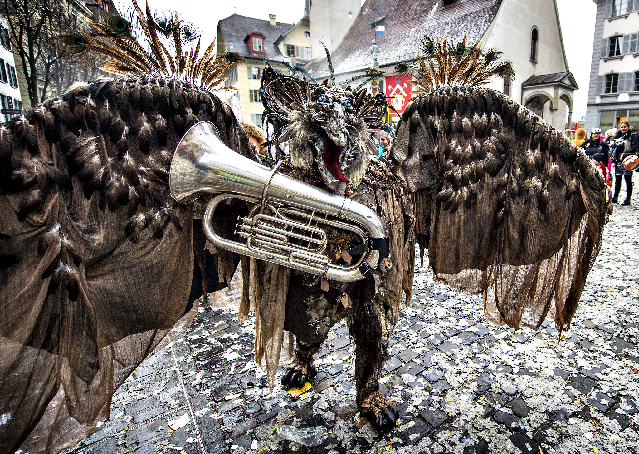 A reveler in a carnival costume attends the opening of the Lucerne carnival in Lucerne, Switzerland, on the so-called dirty Thursday, Feb. 27, 2014.