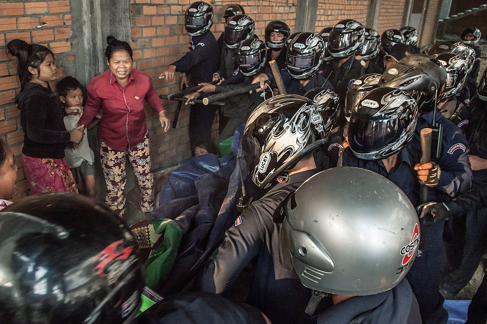 ***BESTPIX*** Forced Eviction Turns Violent In Phnom Penh...PHNOM PENH, CAMBODIA - FEBRUARY 14:  A woman and two children are surrounded by police and municipal security forces during clashes with residents of Borei Keila community on February 14, 2014 in Phnom Penh, Cambodia.  A building which has been occupied for the last two days has been raided by the Cambodian Security forces who sought to forcibly evict the residents. . Early on the morning of Valentine's Day, the road leading into Borei Keila was blocked by riot police, military police, and municipal security guards, who had been deployed to remove all of the families which had occupied the building. Over the course of the violent eviction, at least 6 people were injured, including a woman who was 6 months pregnant. Two days before, on Wednesday, more than 150 people, who had been evicted from their former homes in Borei Keila in January 2012, had moved into the building. The housing building had been promised to them in 2003, as part of a land sharing agreement when the land of Borei Keila had been leased to a private company. The families who had chosen to stay in Borei Keila were violently evicted in 2012 by over 100 security forces, who destroyed more than 200 homes.
