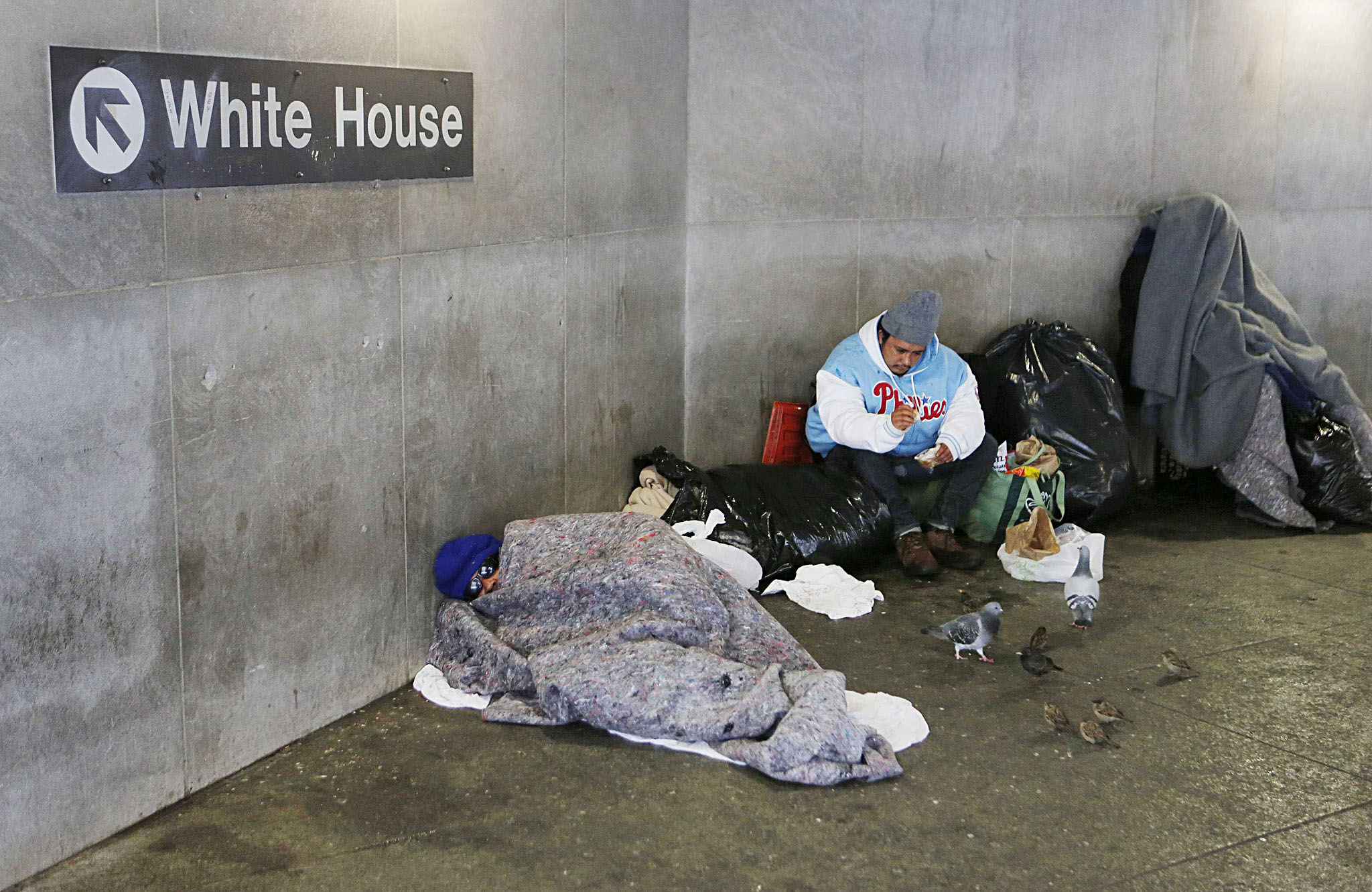 Homeless people bundle up at the McPherson Square Metrorail stop near the White House after the region was pounded with snow overnight around Washington...Homeless people bundle up at the McPherson Square Metrorail stop near the White House after the region was pounded with snow overnight around Washington, February 13, 2014.    REUTERS/Larry Downing