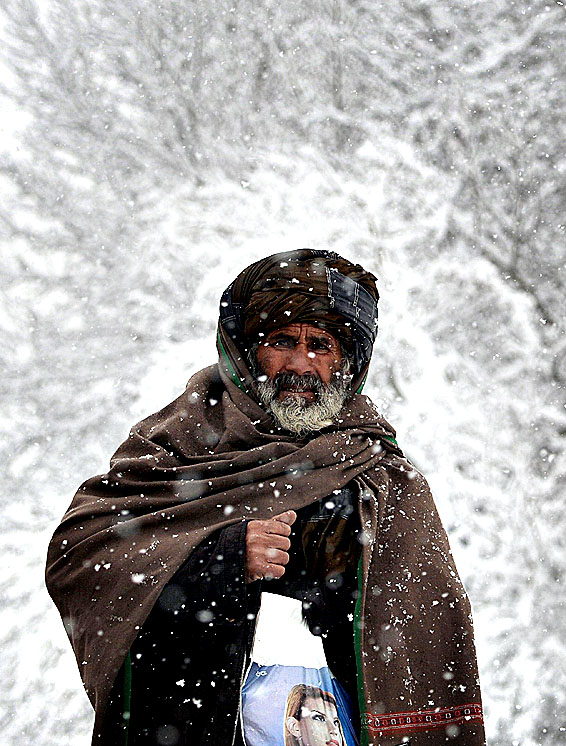 An Afghan resident walks during snowfall in Kabul on February 6, 2014. The Afghan capital has experienced its second heavy snowfall of the winter.
