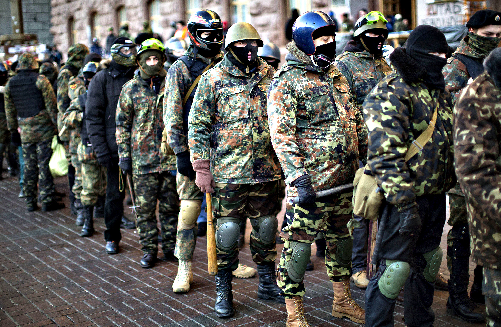 Opposition supporters in military uniforms and carrying sticks as weapons, line up in front of the city council building before marching in central Kiev, Ukraine, Tuesday, Feb. 4, 2014. Ukraine's parliament convenes amid tensions as the country's political crisis persists into its third month. Opposition lawmakers seek to push through a measure for broad amnesty for people arrested in the protests that have gripped the capital, but prospects of passage appear unpromising.