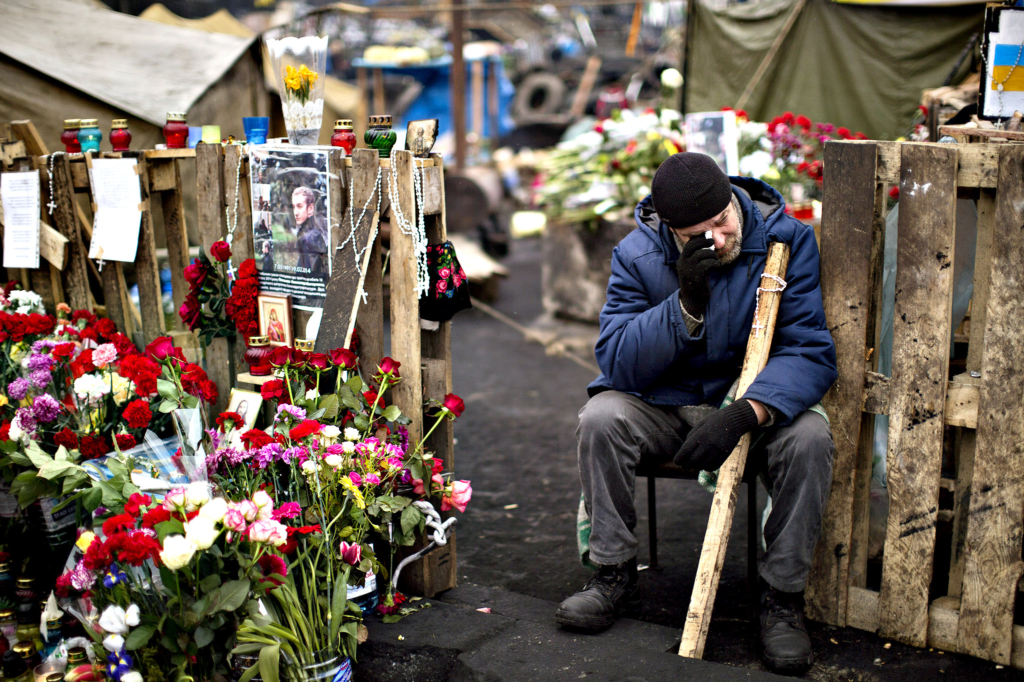 An anti-Yanukovych protester cries near a memorial for the people killed in clashes with the police at Kiev's Independence Square, the epicenter of the country's current unrest, Ukraine, Tuesday, Feb. 25, 2014. The Ukrainian parliament on Tuesday delayed the formation of a new government, reflecting political tensions and economic challenges following the ouster of the Russia-backed president. Parliament speaker Oleksandr Turchinov, who was named Ukraine's interim leader after President Viktor Yanukovych fled the capital, said that a new government should be in place by Thursday, instead of Tuesday, as he had earlier indicated.