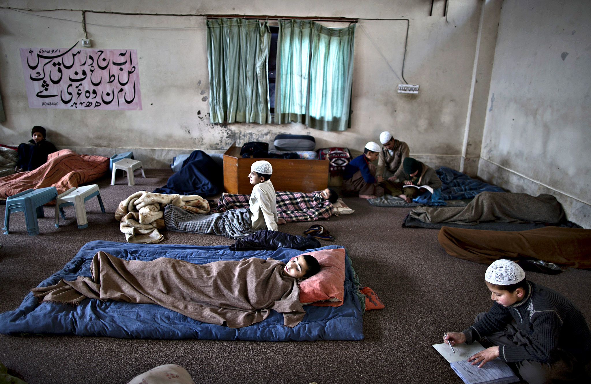 Pakistani students of a madrassa, or Islamic school, some sleeping while others study, in a Mosque in Islamabad, Pakistan, Monday, Feb. 24, 2014. Islamic schools form an important function within the Pakistani educational system, providing for many Pakistanis, the only educational institution they attend.
