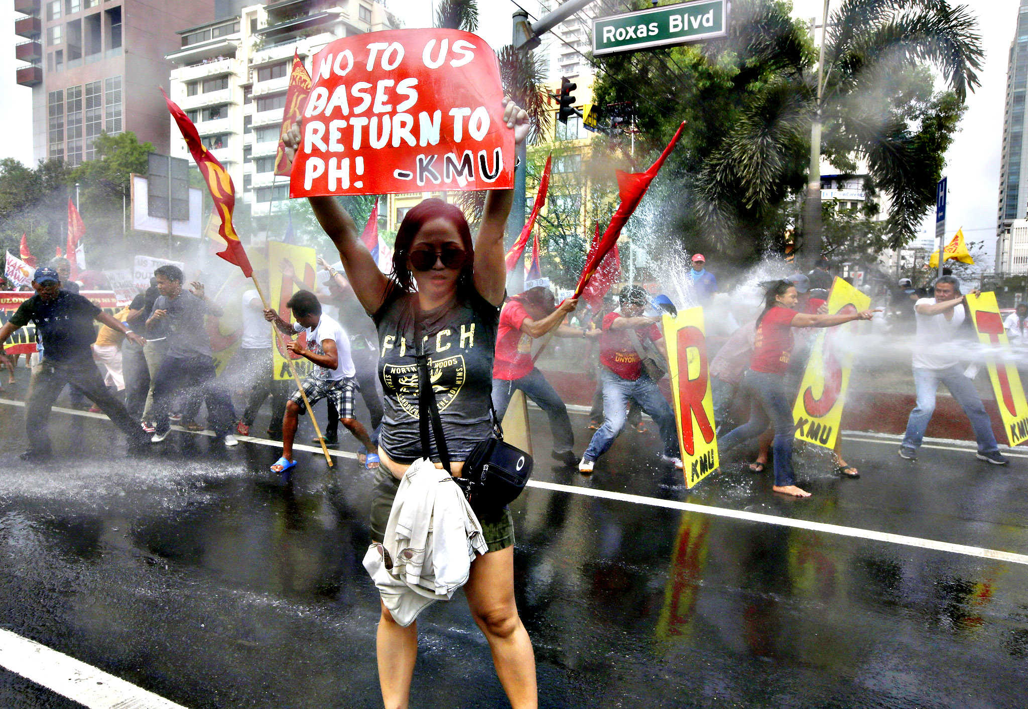 Firemen spray their water cannon at protesters who are forcing their way closer to U.S. Embassy in Manila, Philippines, Tuesday, Feb. 25, 2014 during a protest against the forthcoming visit of U.S. President Barack Obama. The protesters were also calling for the pullout of U.S. troops in the country under the Visiting Forces Agreement