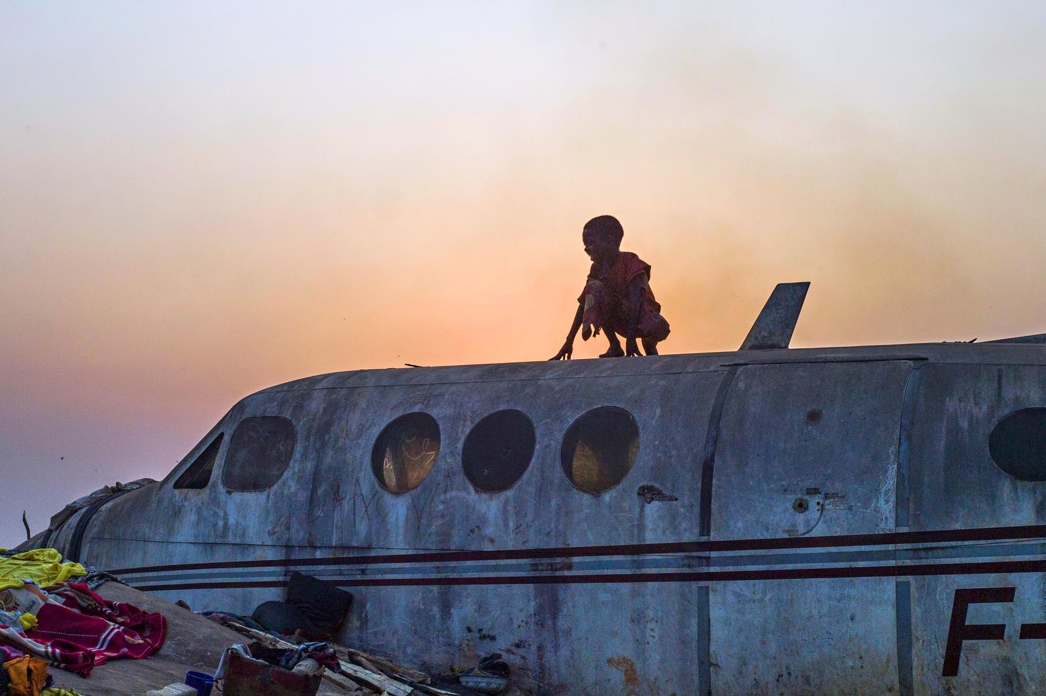A boy stands on an airplane in the Christian Mpoko refugee camp
