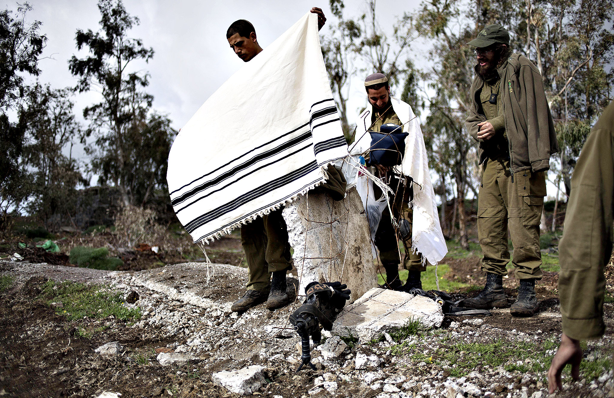 Israeli soldiers of the Golani brigade with prayer shawls after night training near the border with Syria in the Israeli-controlled Golan Heights, Wednesday, Feb. 26, 2014. Hezbollah says Israel carried out an airstrike targeting its positions in Lebanon near the border with Syria earlier this week, claiming it caused damage but no casualties. The Wednesday statement was the group's first acknowledgement of the reported Monday night airstrikes.