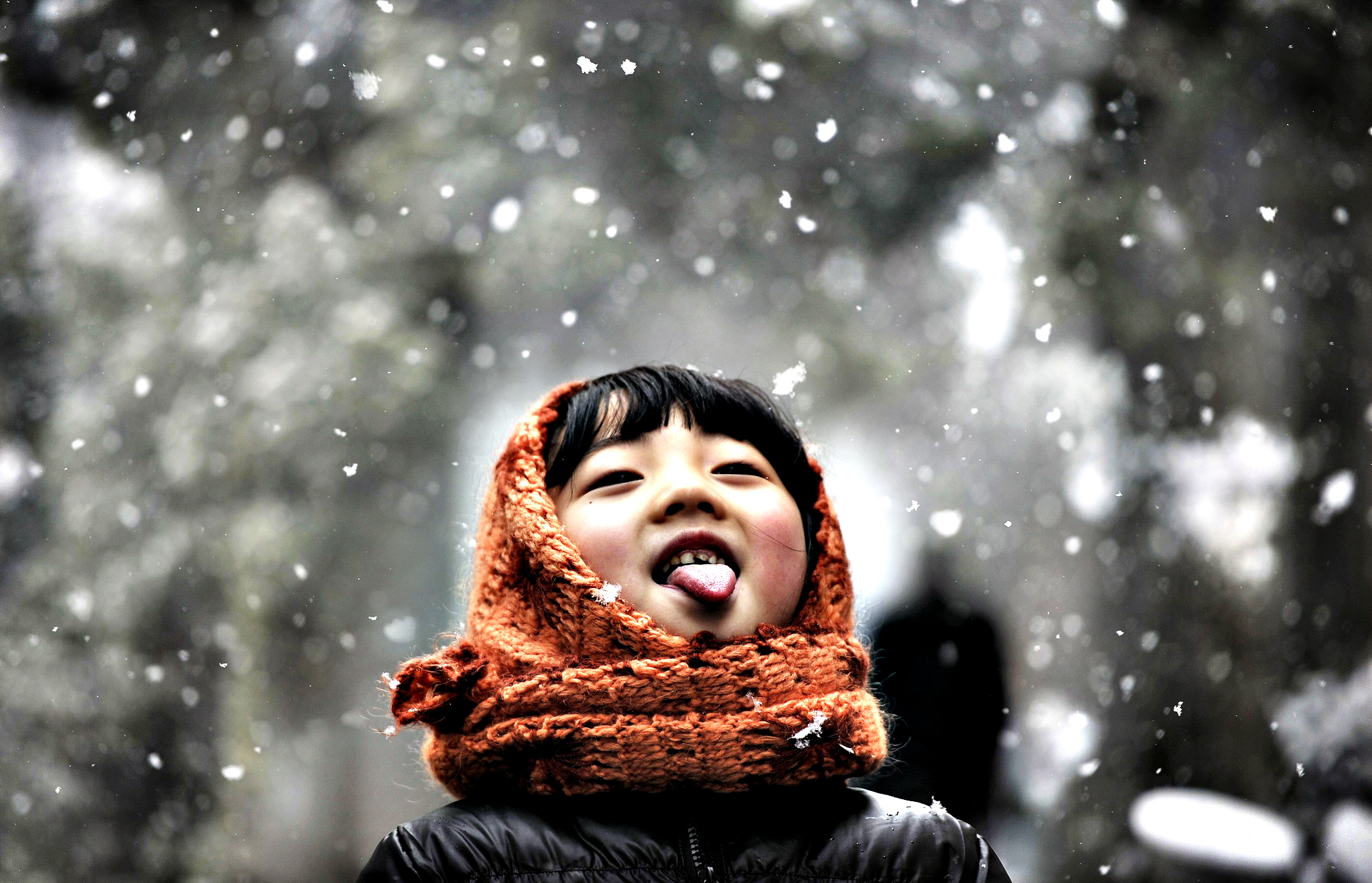 A girl sticks out her tongue during snowfalls on a street in Hefei, Anhui province February 13, 2014.