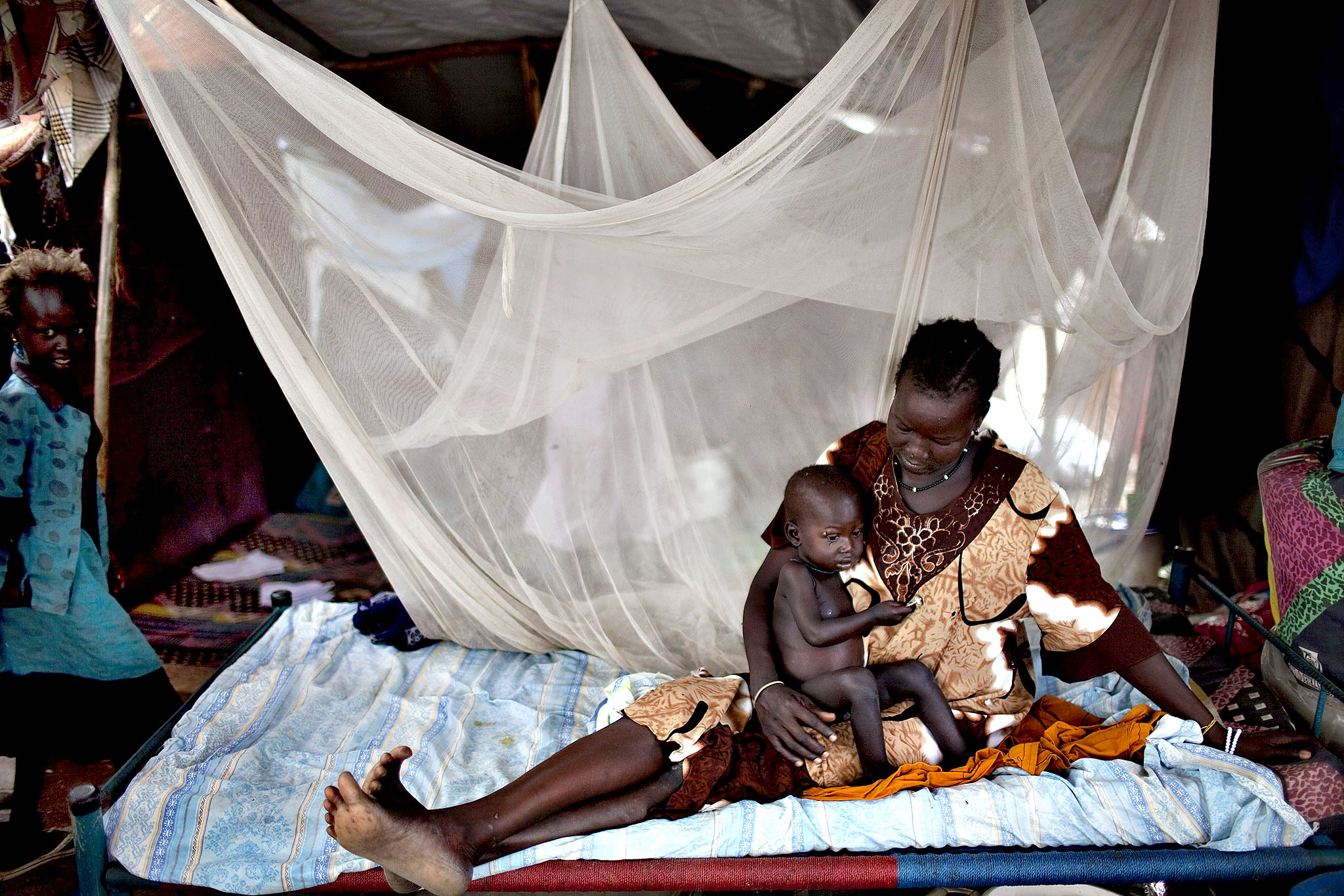 A South Sudanese woman rests on a bed together her son in a IDP camp for the Nuer ethnic group inside the UNMISS compound in Bor, South Sudan, on February 27, 2014. War crimes have been committed by all sides in conflict-wracked South Sudan, Human Rights Watch said Thursday, reporting widespread atrocities in weeks of carnage in the world's youngest nation. Thousands have been killed and almost 900,000 forced from their homes by over two months of battles between rebel and government forces, backed by troops from neighbouring Uganda.