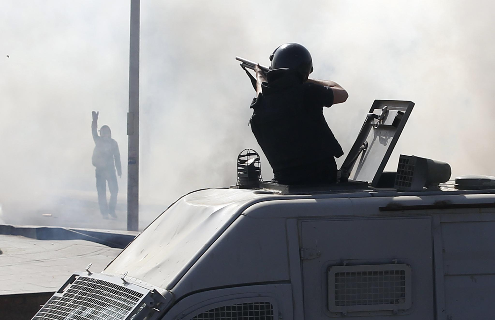 A special forces police officer fires rubber bullets during a demonstration at the front of Cairo University