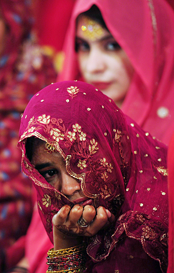 A Pakistani bride looks on during a mass...A Pakistani bride looks on during a mass-wedding ceremony in Karachi on late March 24, 2014. Some 115 couples participated in the mass-wedding ceremony organised by a local charity welfare trust. AFP PHOTO / ASIF HASSANASIF HASSAN/AFP/Getty Images