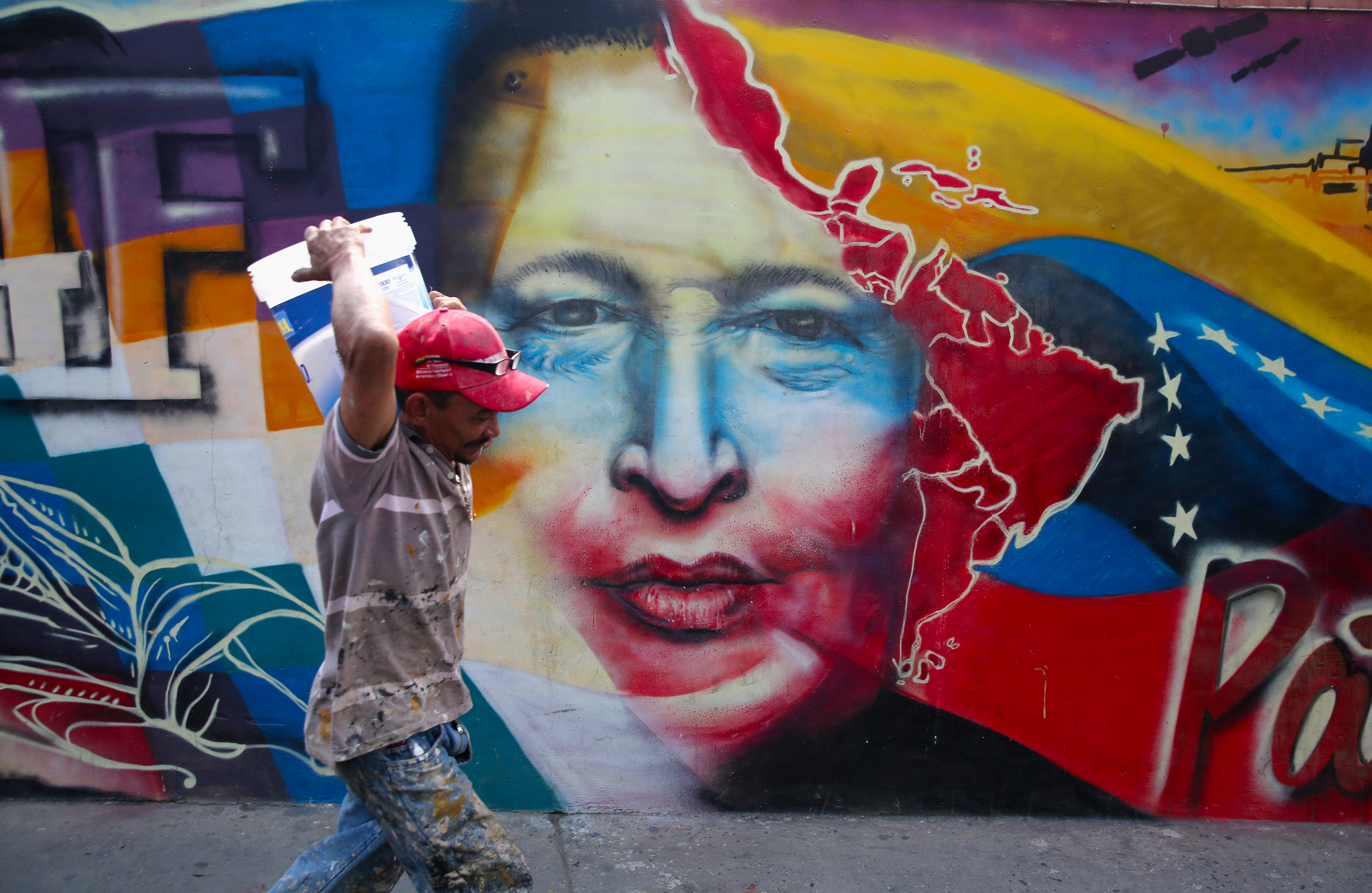 Venezuelans Loyal To Former President Hugo Chavez Prepare To Mark One Year Anniversary Of His Death...CARACAS, VENEZUELA - MARCH 04:  A worker passes a mural of Hugo Chavez at the military barracks where the former Venezuelan president is entombed on March 4, 2014 in Caracas, Venezuela. Workers made last minute preparations for Wednesday's ceremony marking the first anniversary of Chavez' death on March 5, 2013. The anniversary has been marred by three weeks protests against the government of Chavez' chosen successor Nicolas Maduro. (Photo by John Moore/Getty Images)