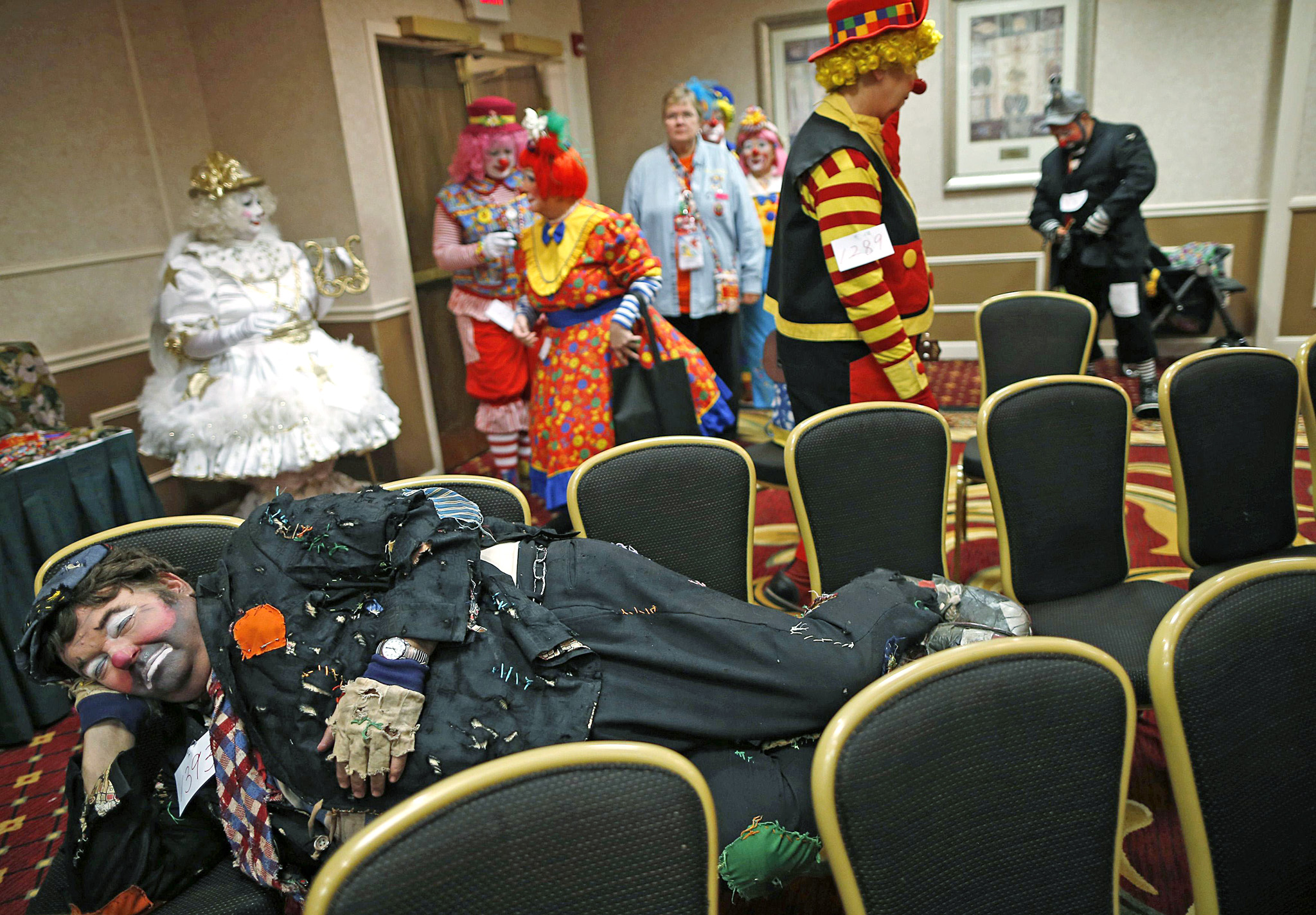 Craig Short lays on chairs as he waits for a competition to begin at the World Clown Association's annual convention in Northbrook...Craig Short lays on chairs as he waits for a competition to begin at the World Clown Association's annual convention in Northbrook, Illinois, March 26, 2014. Hundreds of clown performers from around the world gathered at the event to attend seminars, performances, and competitions. Picture taken March 26, 2014.  REUTERS/Jim Young