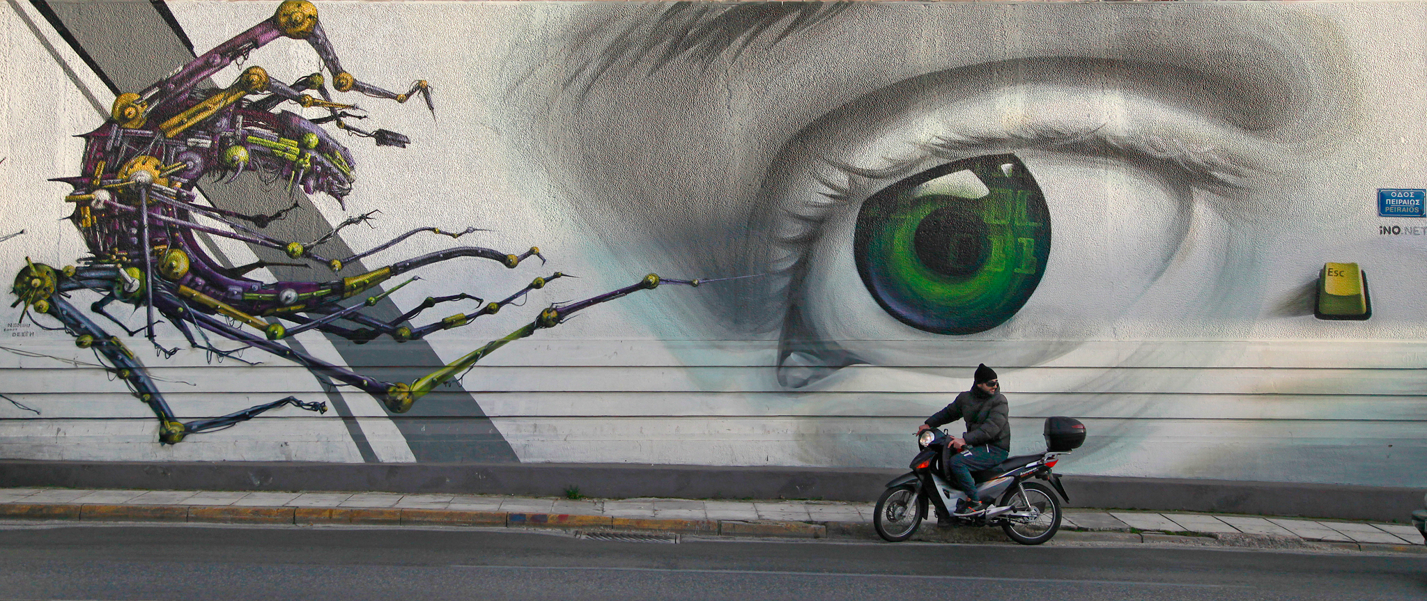 In this photo taken on Thursday Feb. 20, 2014, a motorcyclist passes the work 'Access Control' by Greek street artist iNO, on central Pireos Street in Athens. Greece has attracted international street artists to its capital, due to the availability of commissioned work and relatively lax anti-graffiti law.