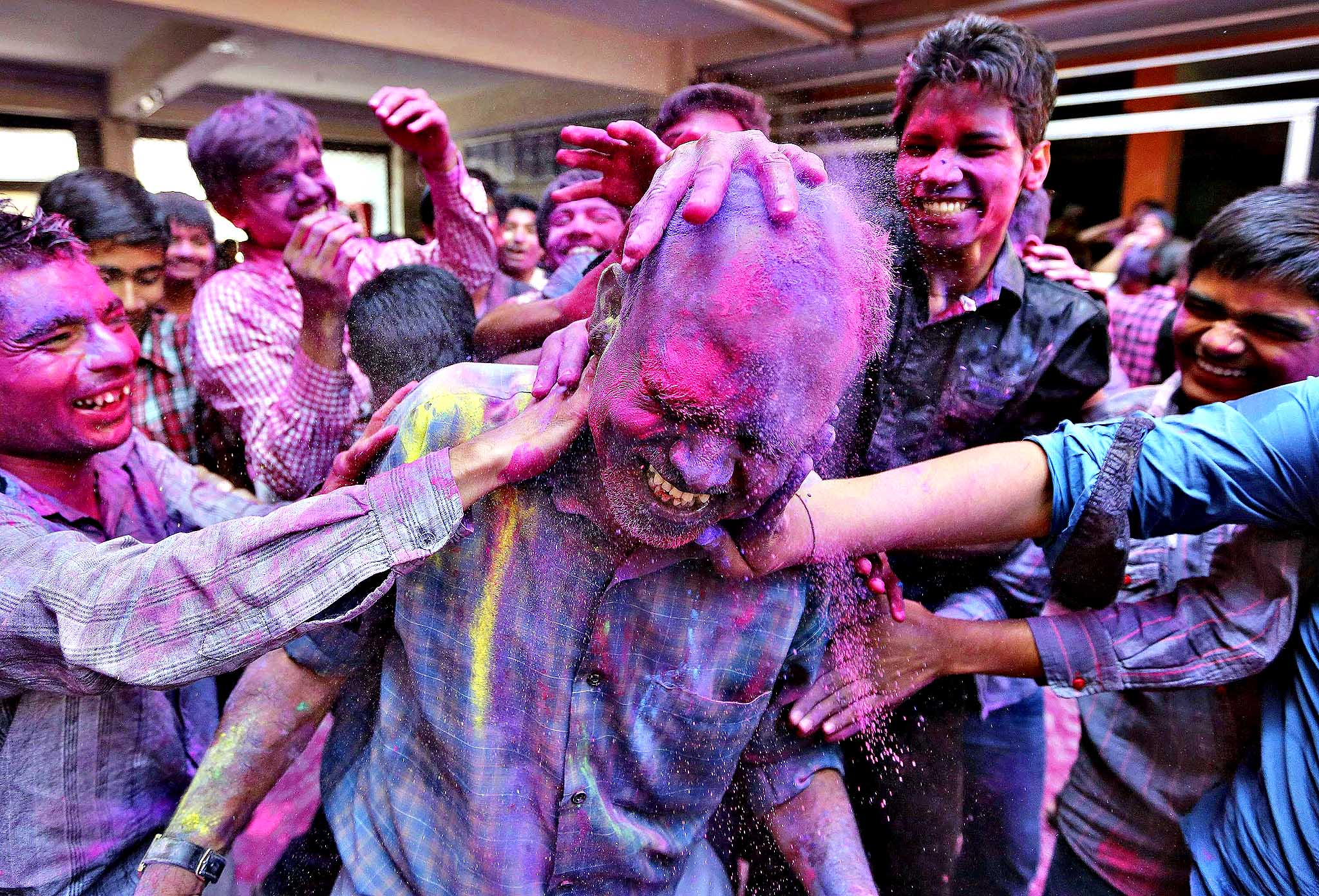 Students apply coloured power onto their teacher's head during Holi celebrations at a school in the western Indian city of Ahmedabad March 14, 2014. Holi, also known as the Festival of Colours, heralds the beginning of spring and is celebrated all over India.