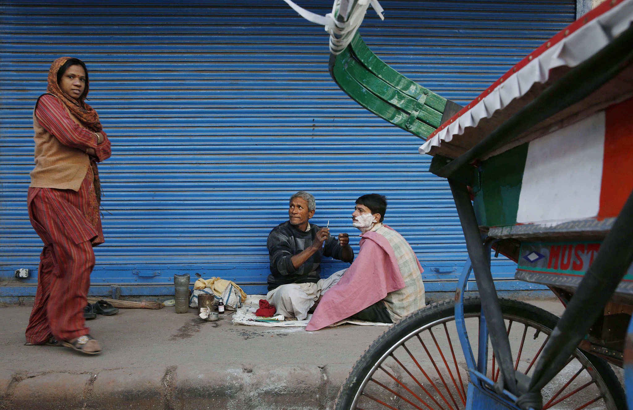 An Indian barber attending to his customer watches a woman in old parts of New Delhi, India, Friday, March 7, 2014.