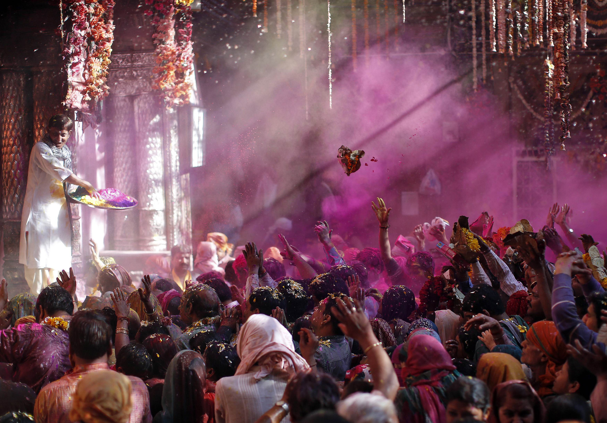 A Hindu priest throws coloured powder and garlands at the devotees during Holi celebrations at Bankey Bihari temple in Vrindavan...A Hindu priest (L) throws coloured powder and garlands at the devotees during Holi celebrations at Bankey Bihari temple in Vrindavan, in the northern Indian state of Uttar Pradesh, March 13, 2014. Holi, also known as the Festival of Colours, heralds the beginning of spring and is celebrated all over India. REUTERS/Ahmad Masood (INDIA - Tags: RELIGION SOCIETY)