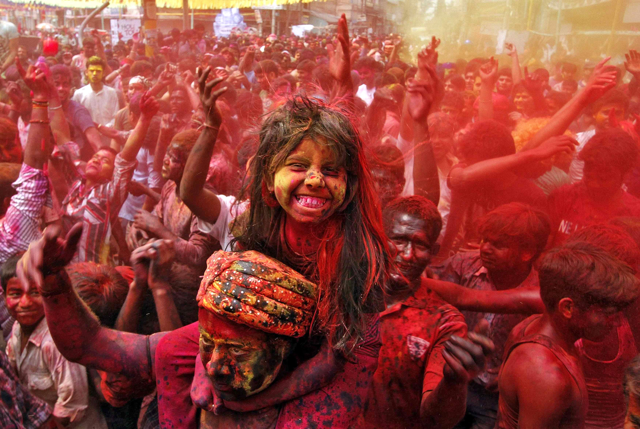 A girl sits on her father's shoulders cheers as she and others daubed in colours dance while celebrating Holi in Guwahati...A girl sits on her father's shoulders cheers as she and others daubed in colours dance while celebrating Holi in the northeastern Indian city of Guwahati March 17, 2014. Holi, also known as the Festival of Colours, heralds the beginning of spring and is celebrated all over India. REUTERS/Utpal Baruah
