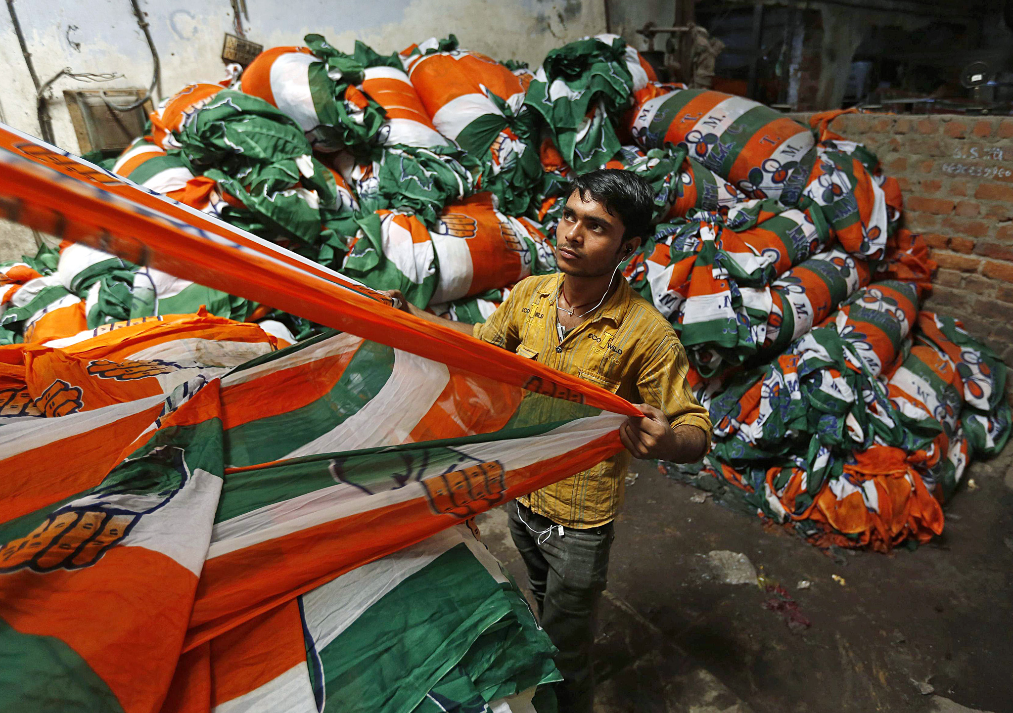 A worker holds a roll of flags of India's ruling Congress party after dying in the colours at a flag manufacturing factory ahead of the 2014 general elections in Ahmedabad...A worker holds a roll of flags of India's ruling Congress party after dying in the colours at a flag manufacturing factory ahead of the 2014 general elections in the western Indian city of Ahmedabad March 25, 2014. India will hold a general election in April and May. REUTERS/Amit Dave
