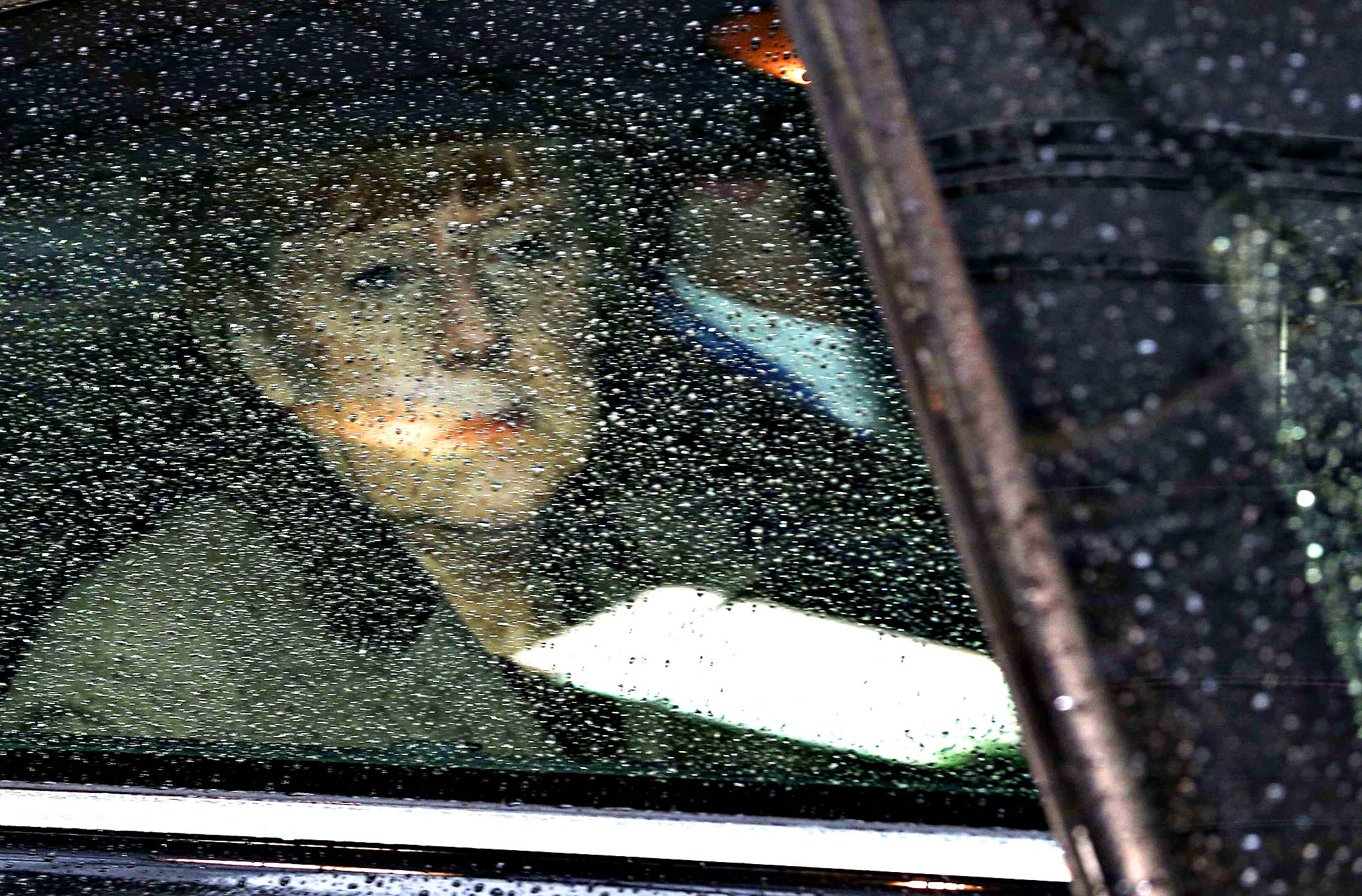 Germany's Chancellor Angela Merkel looks through her window as she arrives at a European Union leaders summit in Brussels March 21, 2014. EU leaders added 12 people to a list of those subject to travel bans and asset freezes for their part in Russia's seizure of Crimea on Thursday and begin preparations for economic sanctions if Russia expands its footprint in Ukraine.