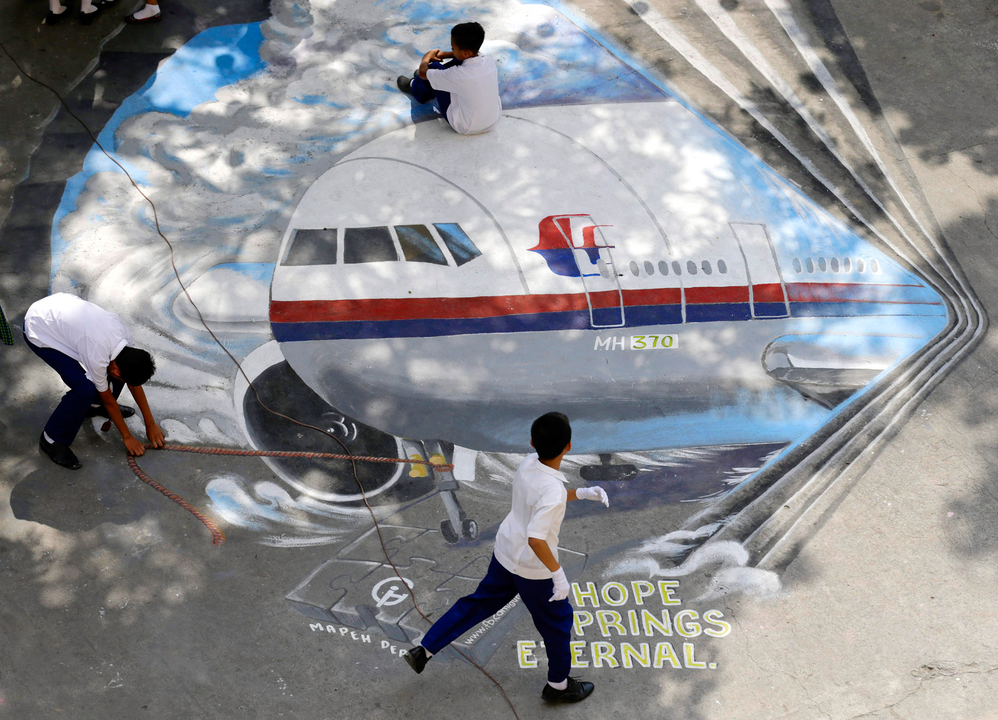 Filipino students are seen on an image of Malaysia Airlines Flight MH370 ....epa04130659 Filipino students are seen on a painting of Malaysia Airlines Flight MH370 at the Benigno Ninoy Aquino High School grounds in Makati City, south of Manila, Philippines, 18 March 2014. Artists from the 'Guhit Visual Arts Group' painted the image to express hope and solidarity for the passengers and crew of the missing Malaysia Airlines flight 370. The search for the Malaysia Airlines passenger jet that disappeared without a trace more than a week ago is expanded to include a wider area spanning from Australia to Kazakhstan.  EPA/FRANCIS R. MALASIG