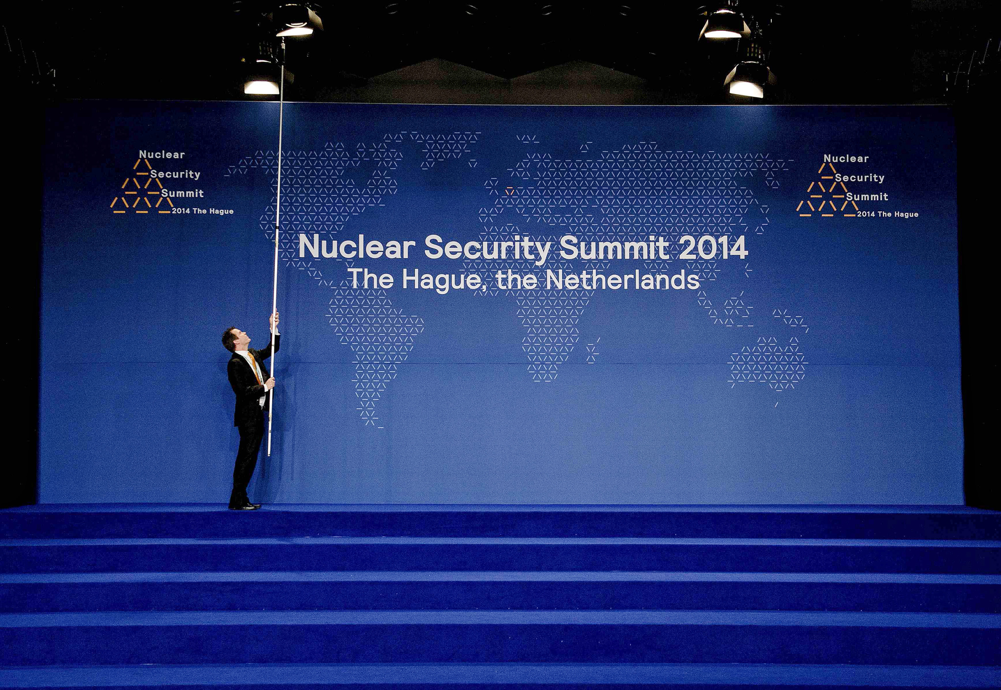 A man adjusts a spotlight above the stage before world leaders' family picture during the Nuclear Security Summit in The Hague...A man adjusts a spotlight above the stage before world leaders' family picture during the Nuclear Security Summit in The Hague March 25, 2014.  REUTERS/Robin Van Lonkhuijsen/Pool (NETHERLANDS  - Tags: POLITICS)