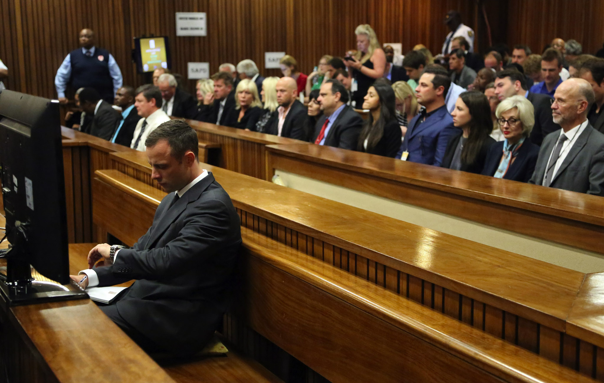 Accused South African Paralympic athlete Oscar Pistorius looks at his watch as the start of his trial is delayed at the high court in Pretoria, South Africa.,