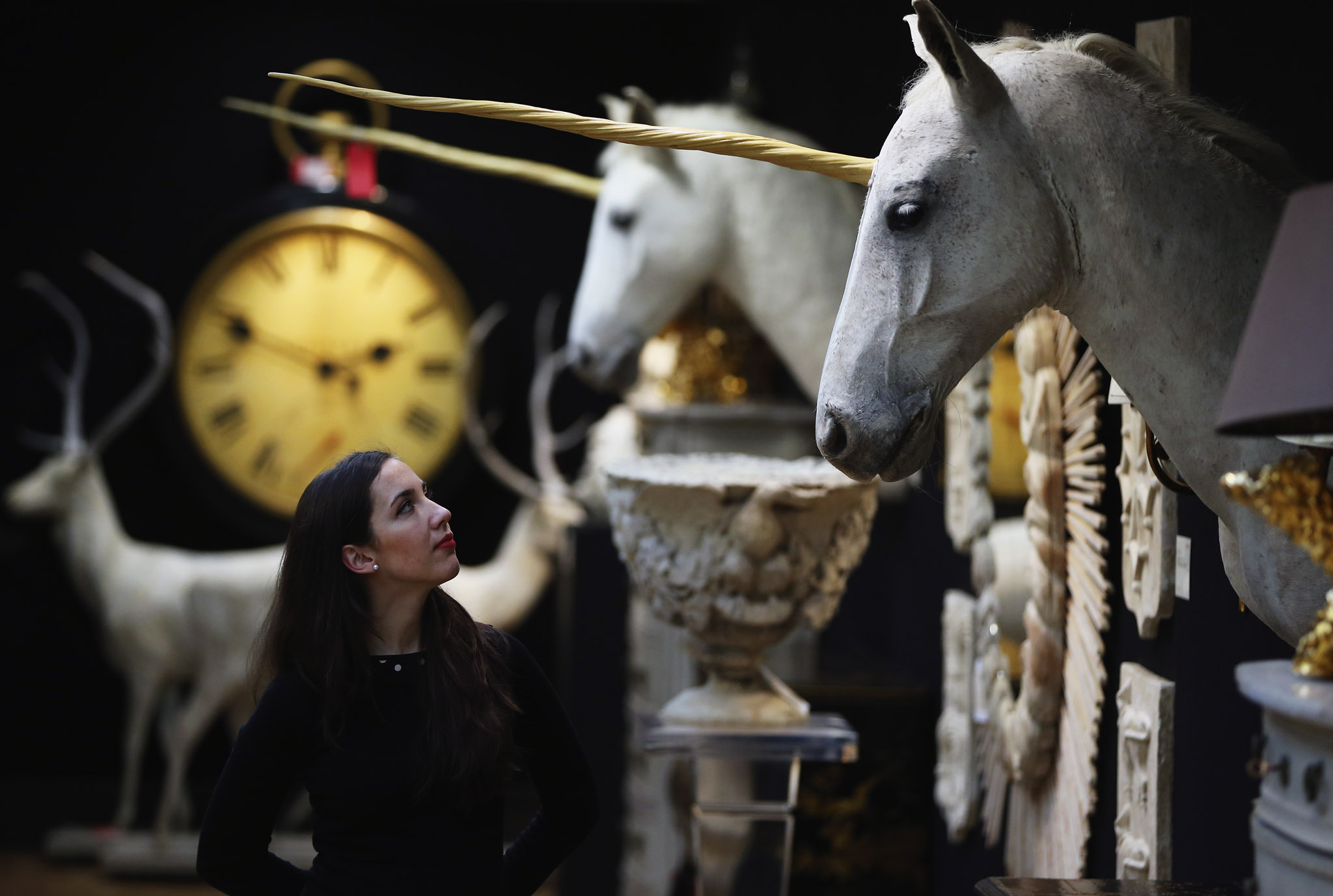 A Christie's employee poses in front of one of two 'Unicorn Heads' at Christie's auction house on in London, England. The items make up part of the Les Trois Garcons' collection which will be sold at auction on March 5, 2014. The collection is made up of 380 lots from the owners of 'Les Trois Garcons' celebrity restaurant in Shoreditch and their homes.