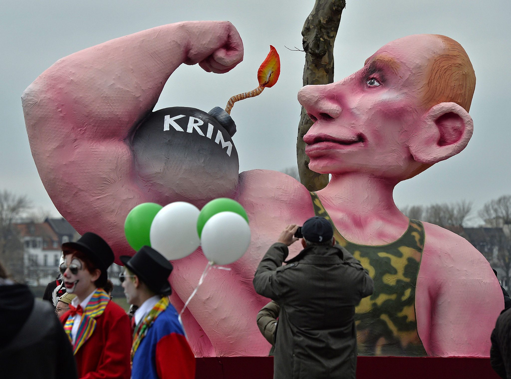 A man takes pictures of a carnival float depicting Russia's president Vladimir Putin  flexing his muscles and a bomb reading ' Crimea', prior to the traditional carnival parade in Duesseldorf, western Germany. The street spectacles in the carnival centers of Duesseldorf, Mainz and Cologne, are watched by hundreds of thousands of people and are the highlight of Germany's carnival season called Rosenmontag (Rose Monday).