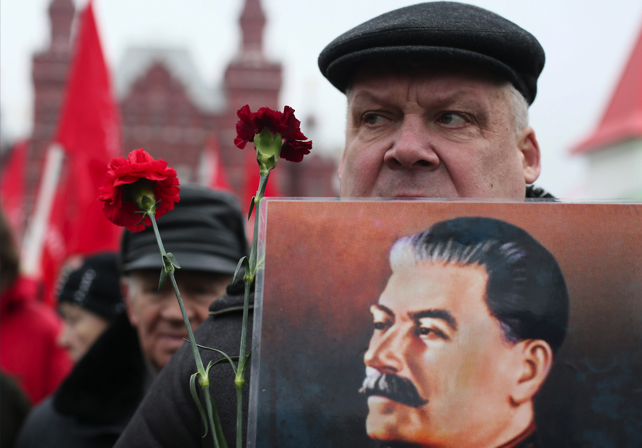 A man holds a portrait of Josef Stalin before laying flowers at the grave of the late Soviet leader during a ceremony to mark the 61th anniversary of Stalin's death in the Red Square in Moscow, Russia.,