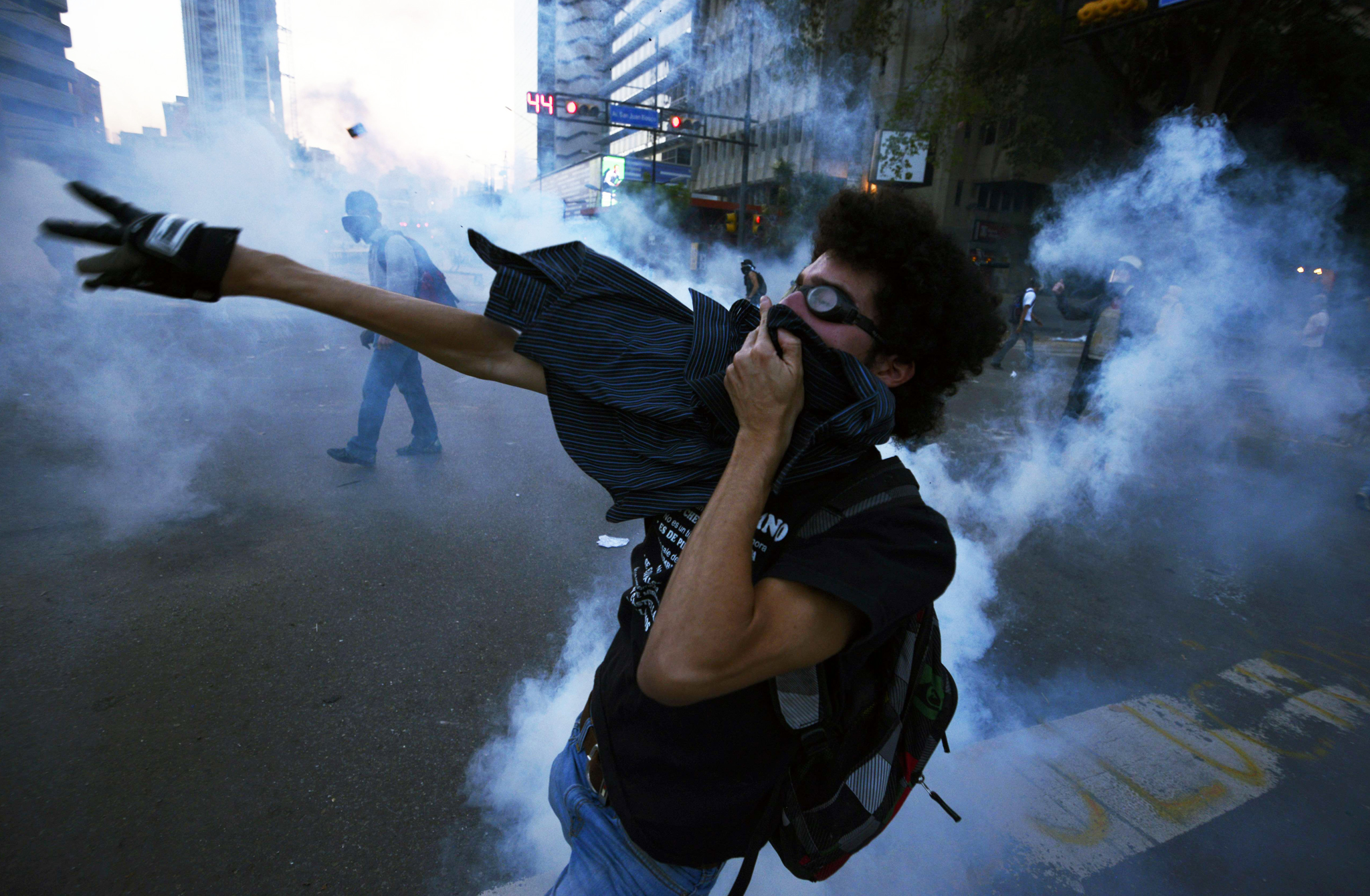 An opposition activist returns tear gas to riot police during a protest against the government of Venezuelan President Nicolas Maduro in Caracas. Venezuela marked the anniversary of Chavez's death with a blend of solemn ceremonies, clashes and a break in relations with Panama over protests dogging his successor's presidency.