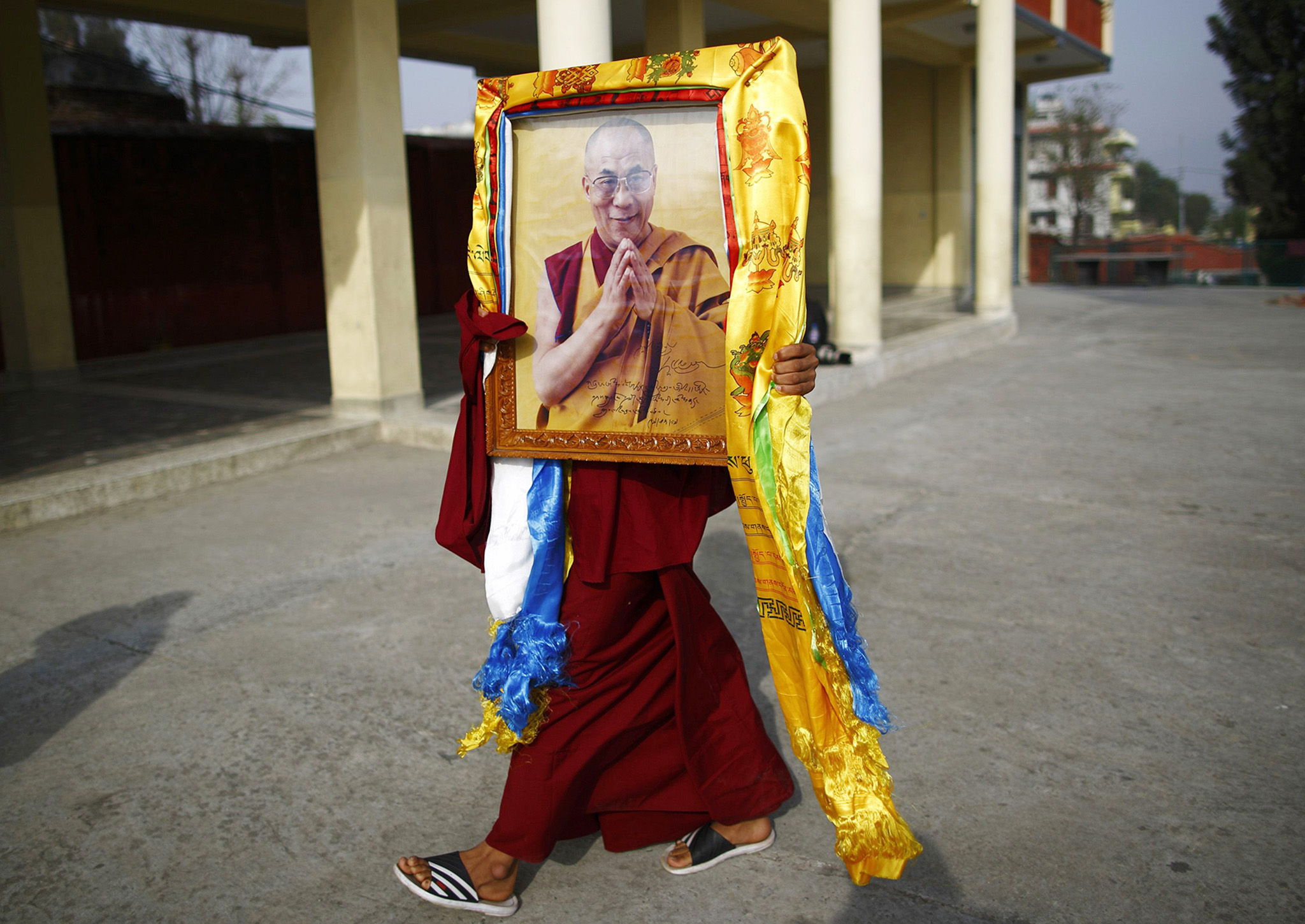 A Tibetan monk carries a portrait of the Dalai Lama during Losar celebrations in Kathmandu