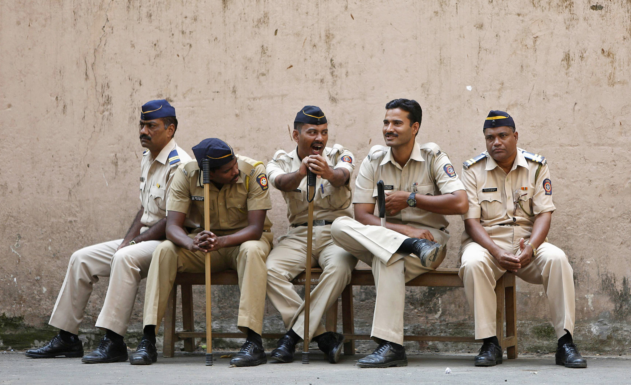 A policeman yawns as he sits with his colleagues outside a court where the case of the gang-rape of a photojournalist was heard in Mumbai...A policeman (C) yawns as he sits with his colleagues outside a court where the case of the gang-rape of a photojournalist was heard in Mumbai March 20, 2014. Four men were found guilty on Thursday of the gang-rape of a photojournalist last year in Mumbai, an attack that sparked street protests in the city and raised fresh questions about attitudes to women in the world's largest democracy. The four men convicted of gang-rape are due to be sentenced on Friday, prosecution lawyer Ujjwal Nikam told reporters outside the Mumbai court where the case was heard. REUTERS/Mansi Thapliyal (INDIA - Tags: CRIME LAW)