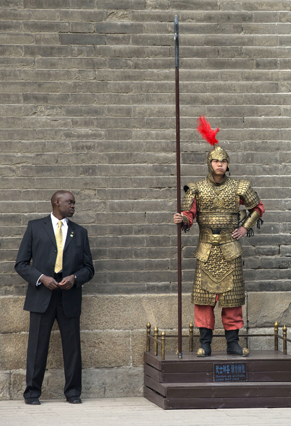 A U.S. secret service officer checks a Chinese performer dressed as an ancient warrior as U.S. first lady Michelle Obama visits a nearby city wall in Xi'an, in northwestern China's Shaanxi province, Monday, March 24, 2014. (AP Photo/Alexander F. Yuan)