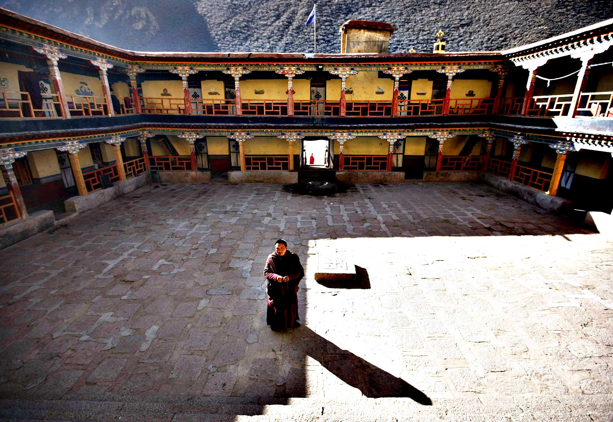 A Tibetan monk stands in the middle of a square at a Tibetan Buddhism school of the Tsurphu Monastery in Doilungdeqen county, Tibet Autonomous Region.