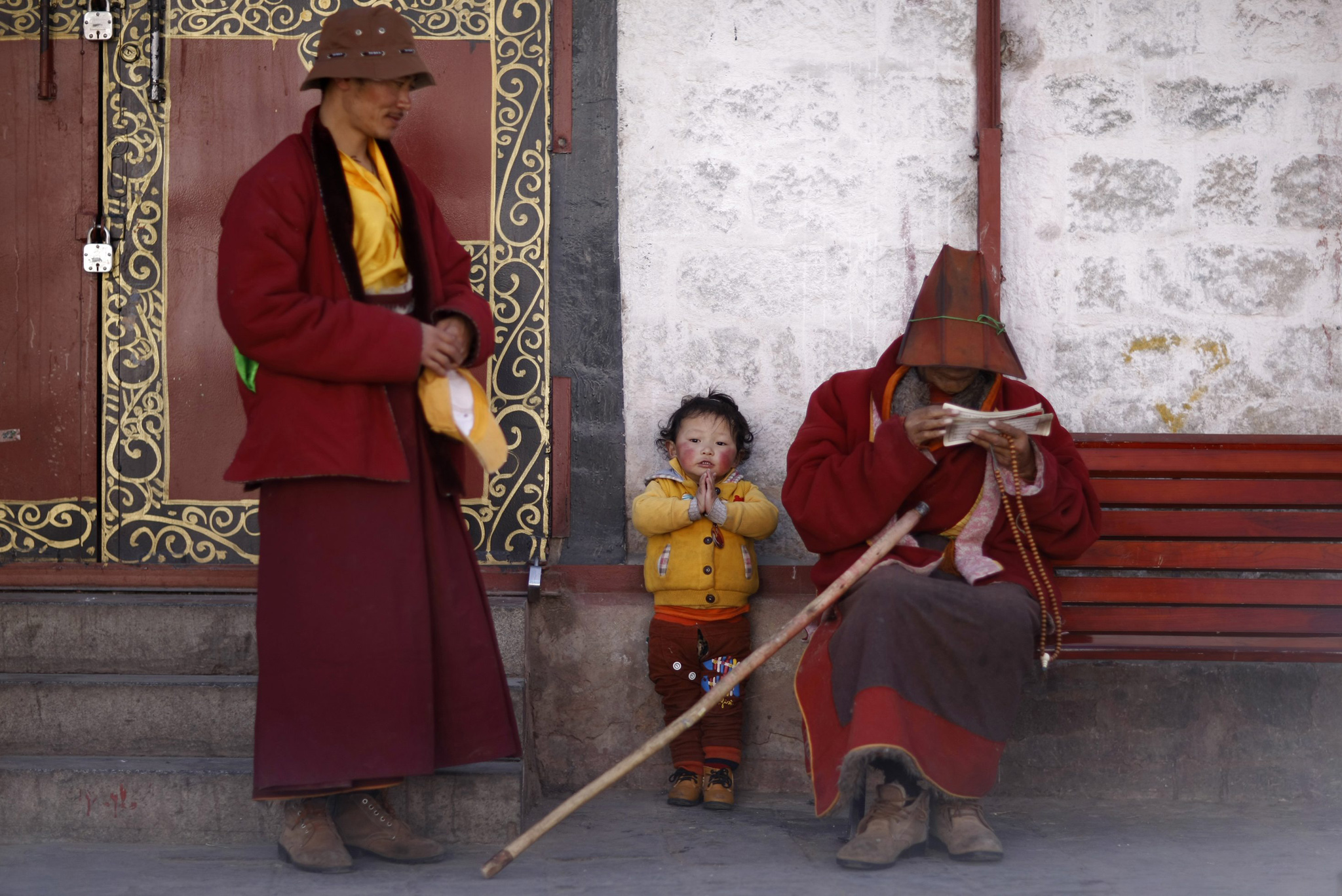 A boy puts his palms together as he rests with his family outside Jokhang Monastery in Lhasa, Tibet autonomous region, March 4, 2014.